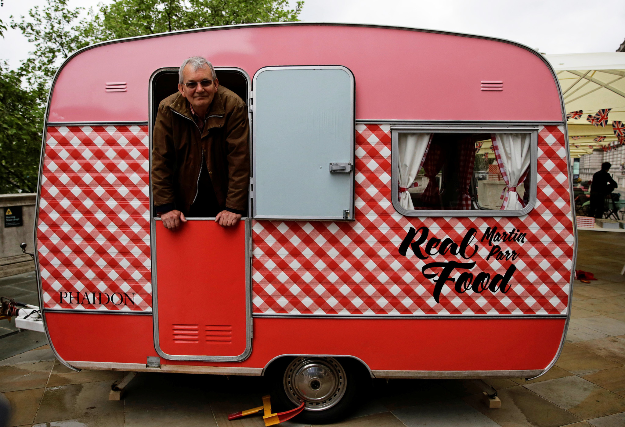 Photographer Martin Parr looks out from his own caravan which is serving food at the Photo London show in London, Britain, May 18, 2016