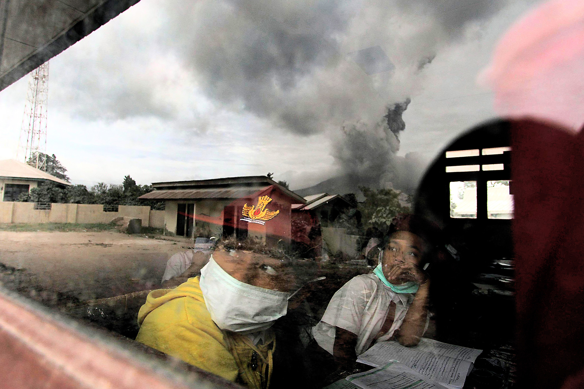 TOPSHOT - Primary school children wear masks while studying in the classroom in Karo district, North Sumatra province, on May 24, 2016, as Mount Sinabung is seen spewing out volcanic ash through the school window reflection.  Indonesian rescuers searched for survivors in scorched villages and devastated farmlands after a volcano erupted in clouds of searing ash and gas, killing seven and leaving others fighting life-threatening burns. / AFP PHOTO / FATIMA ELKAREEMFATIMA ELKAREEM/AFP/Getty Images
