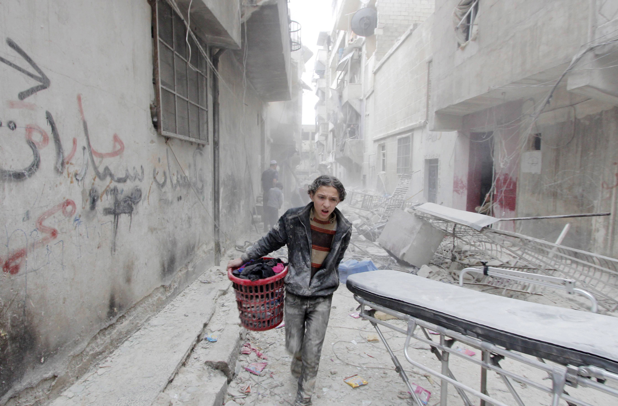 A boy carries his belongings at a site hit by what activists said was a barrel bomb dropped by forces loyal to Syria's President Bashar al-Assad in Aleppo's al-Fardous district, Syria April 2, 2015. REUTERS/Rami Zayat/File Photo