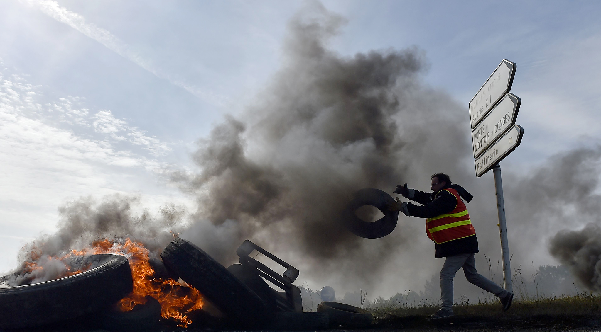 A labour union member sends a tyre upon a pile of tyres set ablaze at a filtering roadblock close to the entrance of the Total refinery of Donges, western France, on May 31, 2016, to protest against the government's planned labour law reforms.    / AFP PHOTO / LOIC VENANCELOIC VENANCE/AFP/Getty Images