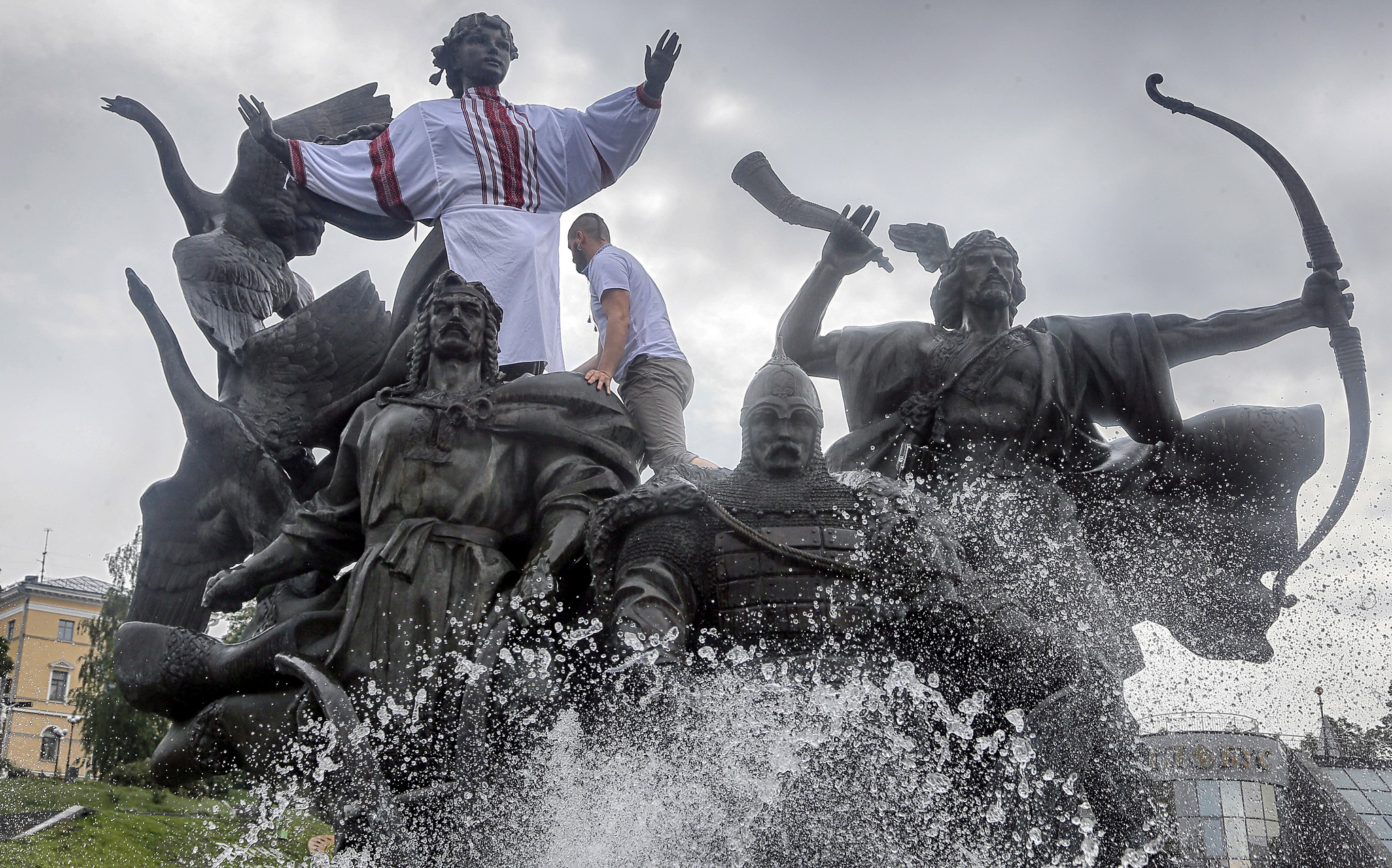 A man dresses a statue figure on the monument dedicated to Kiev city founders, in the national Ukrainian costume called Vyshyvanka,  on the Independence Square in Kiev, Ukraine, Thursday, May 19, 2016.  Ukrainians mark Vyshyvanka Day, named in honour of the Slavic traditional clothing Vyshyvanka. (AP Photo/Efrem Lukatsky)