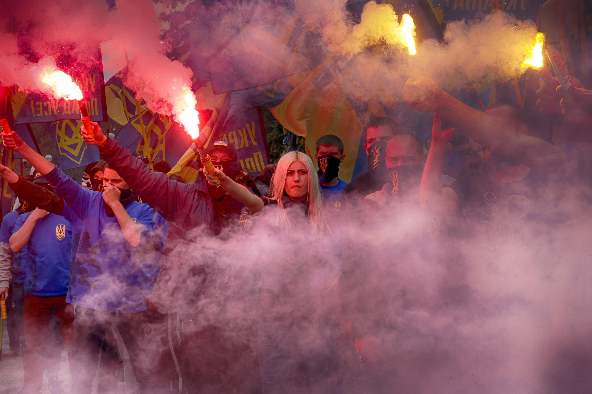 Volunteers of the Azov Civil Corps light flares during rally at the Ukrainian Parliament, Friday, May 20, 2016, against holding local elections in the occupied eastern territories of Ukraine. As part of an internationally brokered peace agreement, Ukraine must hold local elections in two eastern regions controlled by Russian-backed rebels, but there are major concerns about ensuring the vote takes place in a secure and safe atmosphere. (AP Photo/Efrem Lukatsky)