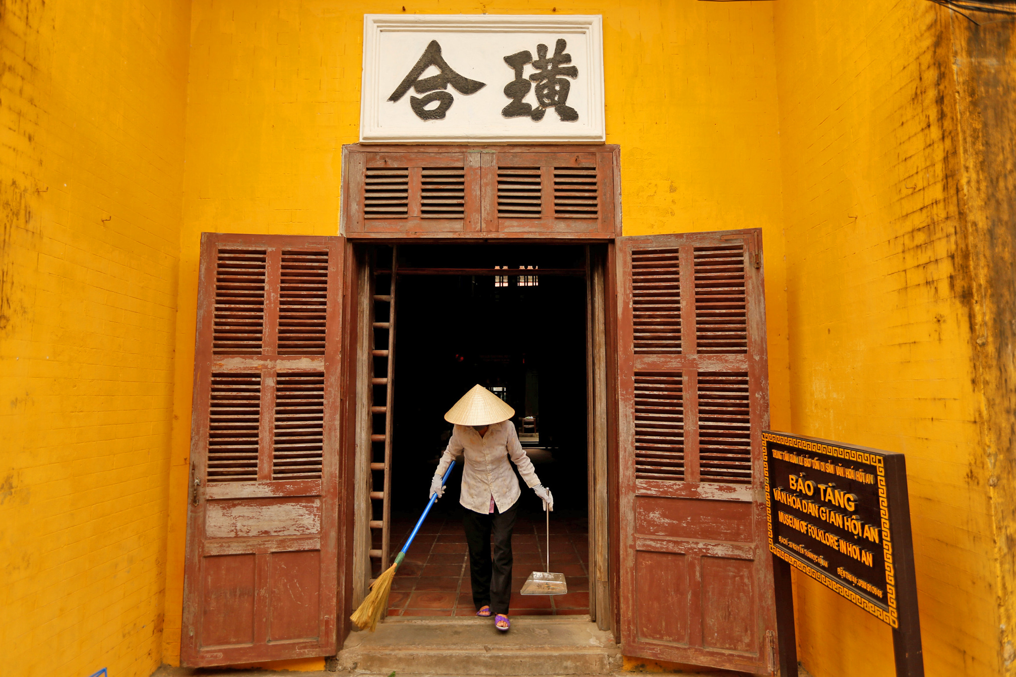 A woman wearing a traditional hat, known as a non la, sweeps an entrance of a museum in Hoi An, Vietnam April 5, 2016. The non la hats are made of readily available materials such as palm leaves, tree bark and bamboo and are visible everywhere in the city, a UNESCO World Heritage site. Hoi An's history as a busy trading port is evident throughout its architecture, a mix of eras and styles, with traditional wooden Vietnamese houses, Chinese temples and French colonial buildings