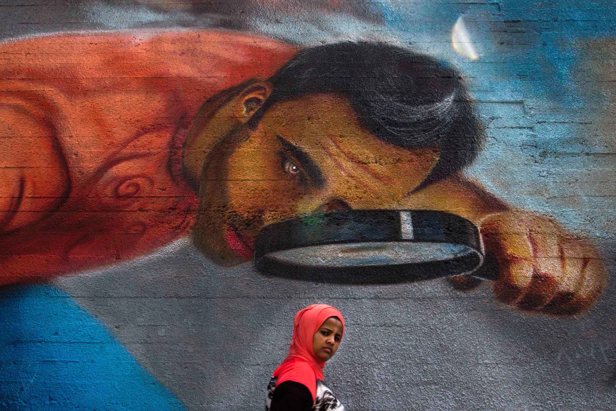 A woman walks past street art in Beirut, Lebano