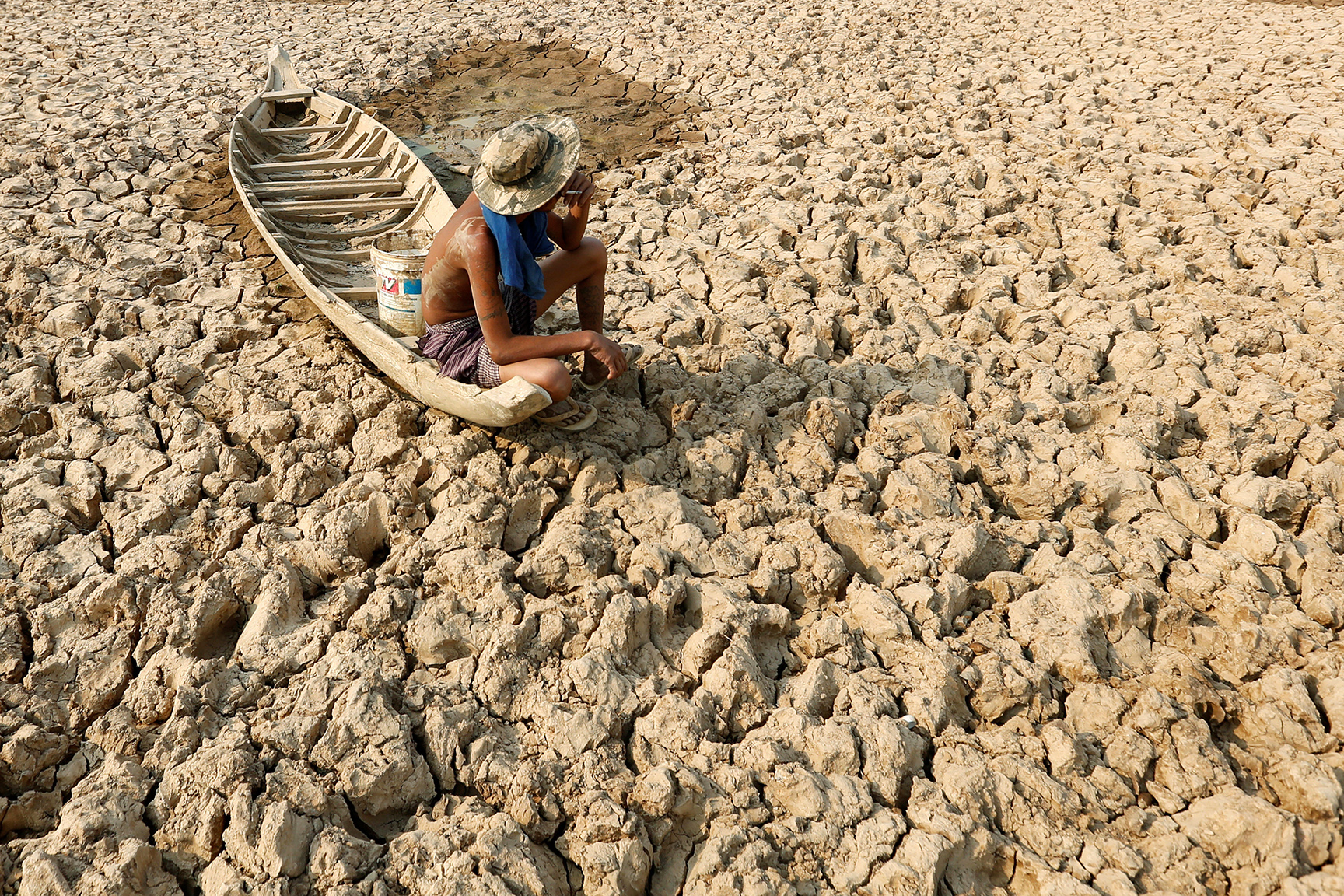 A fisherman sits to smoke on his boat at a Bak Angrout dried up pond at the drought-hit Kandal province in Cambodia