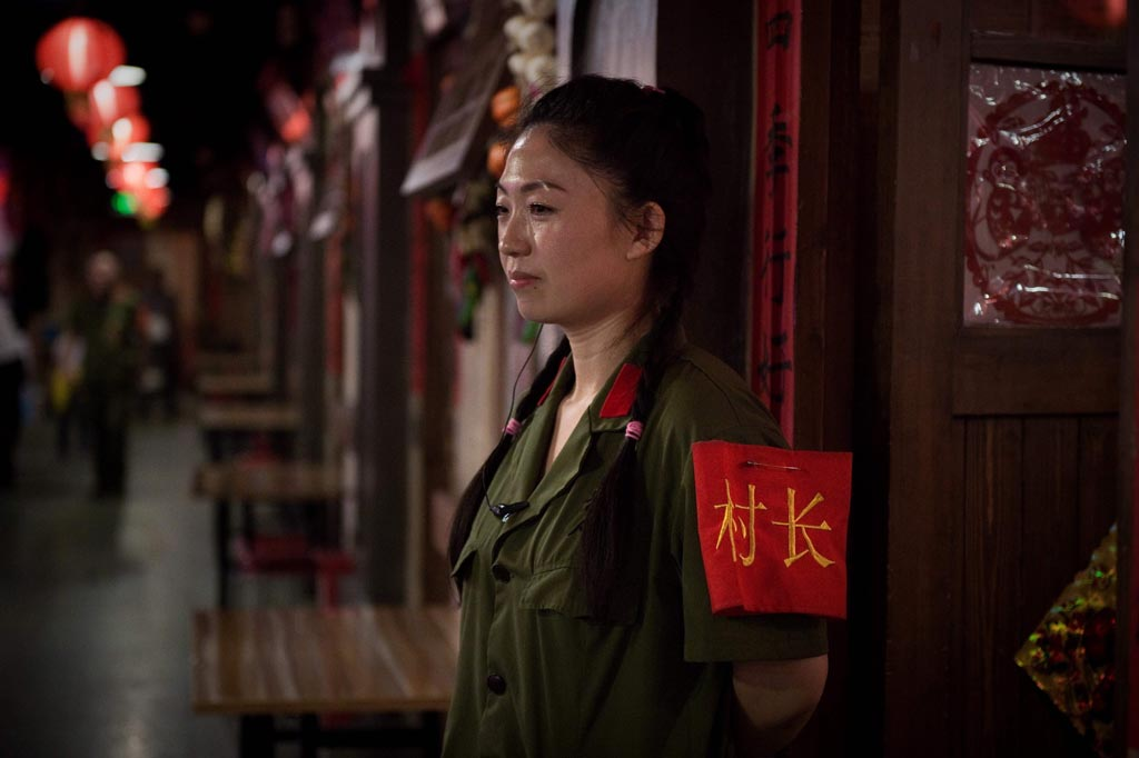 "A waitress with an army-style top and red armband that reads ""village chief"" stands in a restaurant in Beijing"