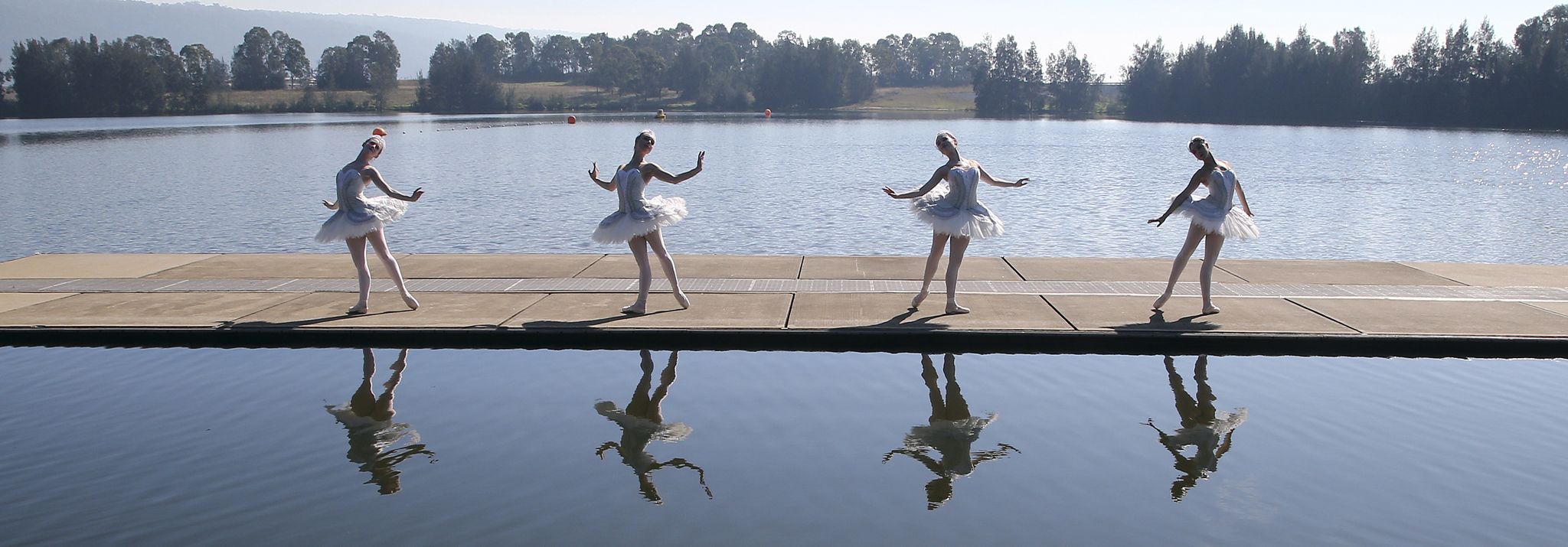 our dancers from The Australian Ballet dressed in white swan tutus pose for photos on floating barge in Penrith Lake in Sydney, Australia