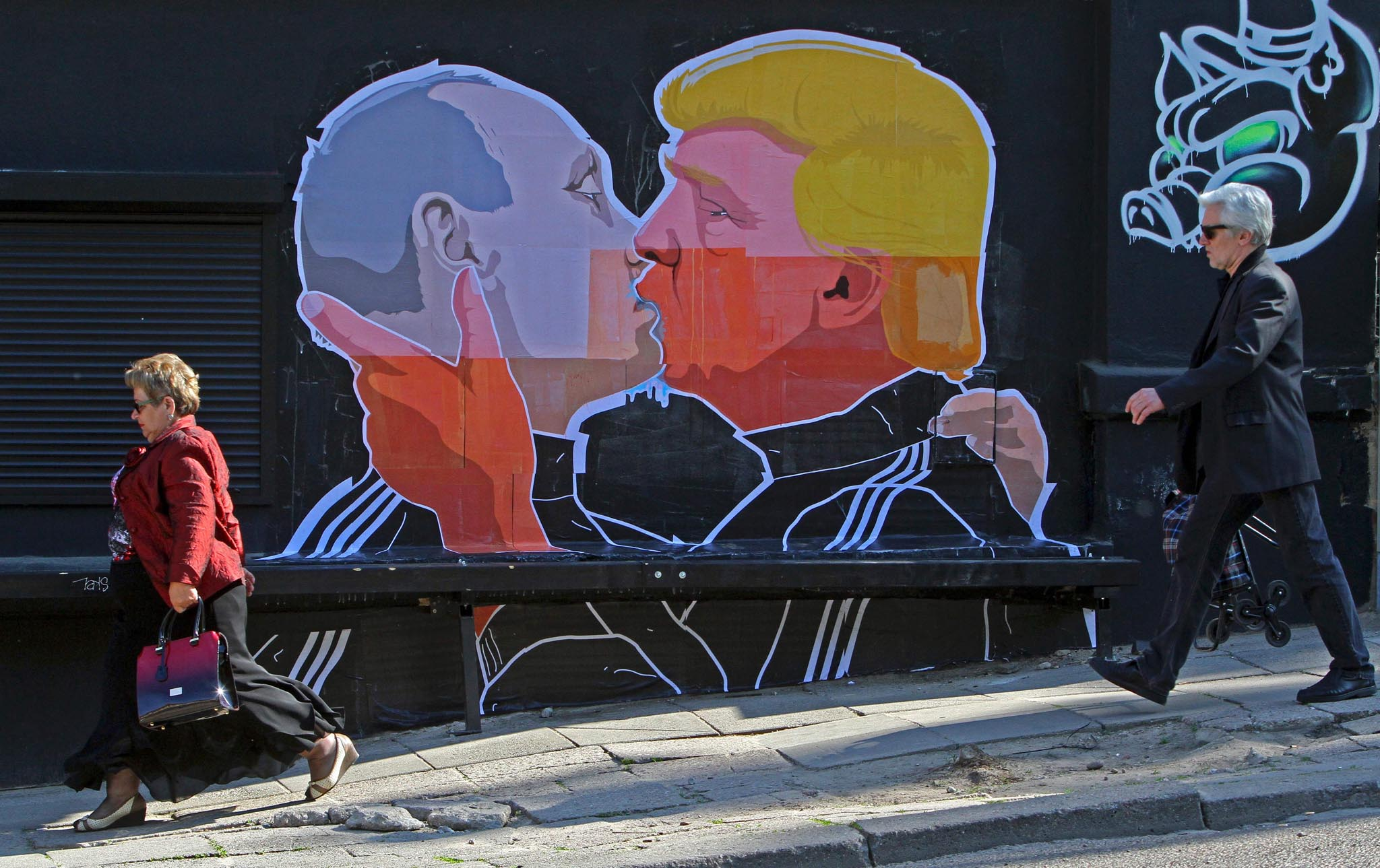 People walk past a mural on a restaurant wall depicting US  Presidential hopeful Donald Trump and Russian President Vladimir Putin greeting each other with a kiss in the Lithuanian capital Vilnius