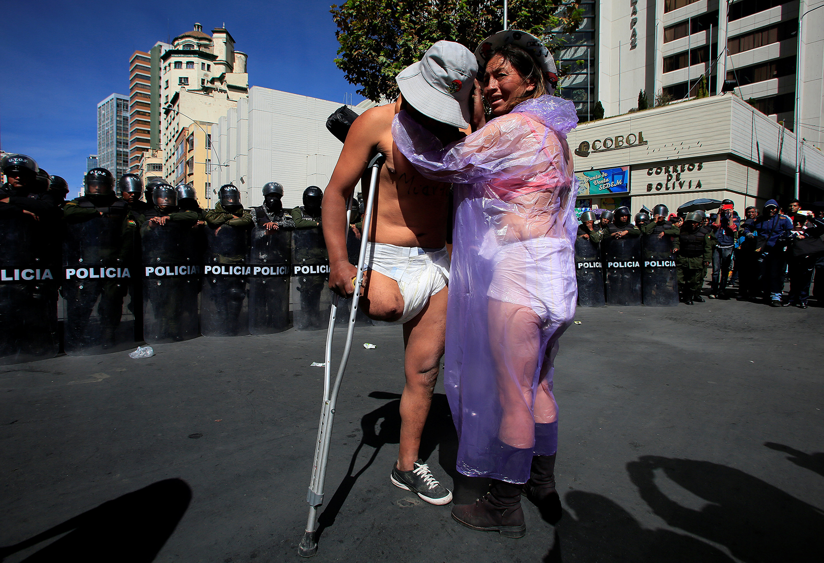 Demonstrators with a physical disability stand in front a riot police barricade during a protest in La Paz