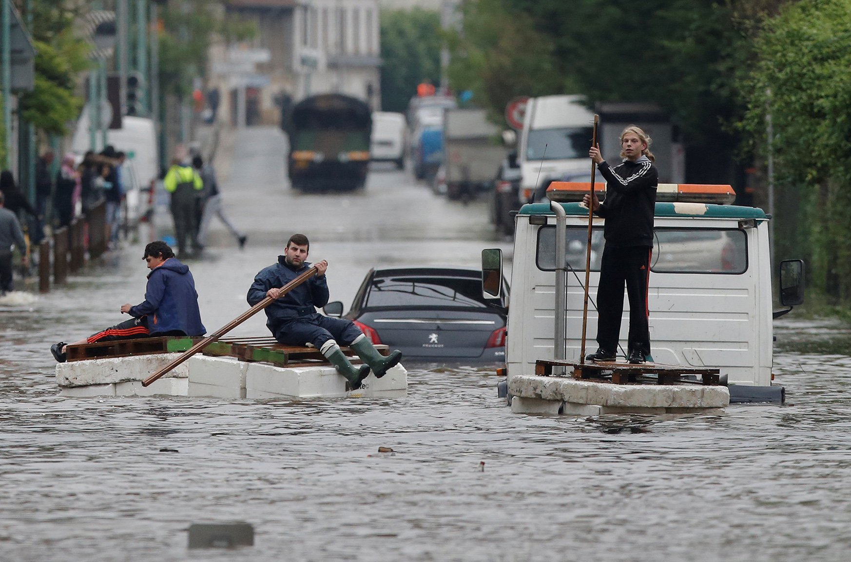 Residents who refused to be evacuated sit on makeshift boats during evacuation operations of the Villeneuve-Trillage flooded suburb in Villeneuve Saint-Georges