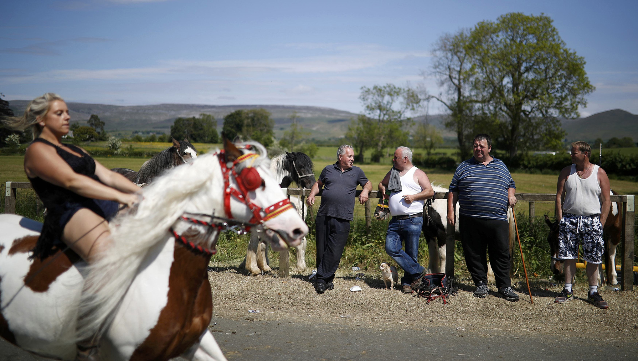 Members of the traveller community watch as horses are ridden along the road during the horse fair in Appleby-in-Westmorland, northern Britain.