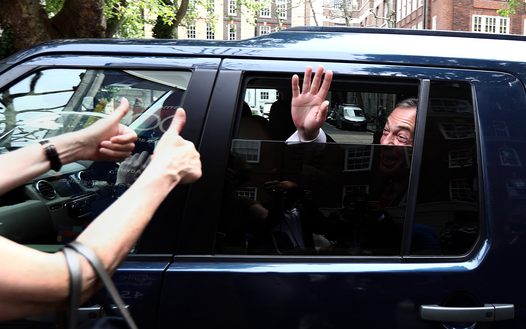 UKIP leader Nigel Farage waves to a supporter as he leaves after unveiling a new campaign poster ahead of a televised debate with the Prime Minister
