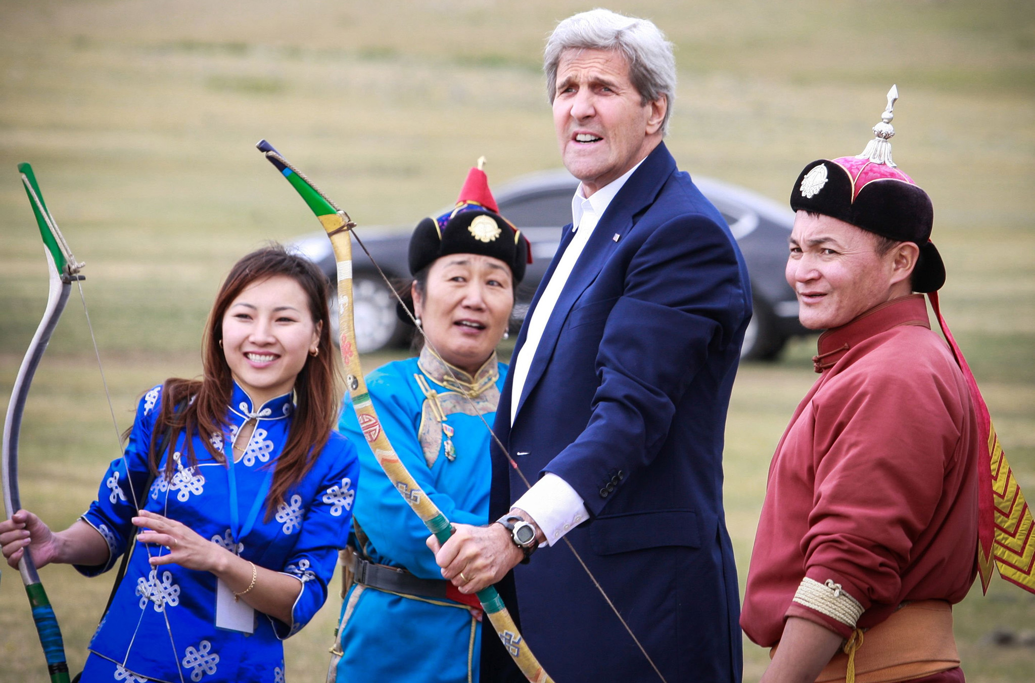 US Secretary of State John Kerry reacts after shooting a bow and arrow as he participates in a Naadam ceremony, a competition which traditionally includes horse racing, Mongolian wrestling and archery, in Ulan Bator, Mongolia.
