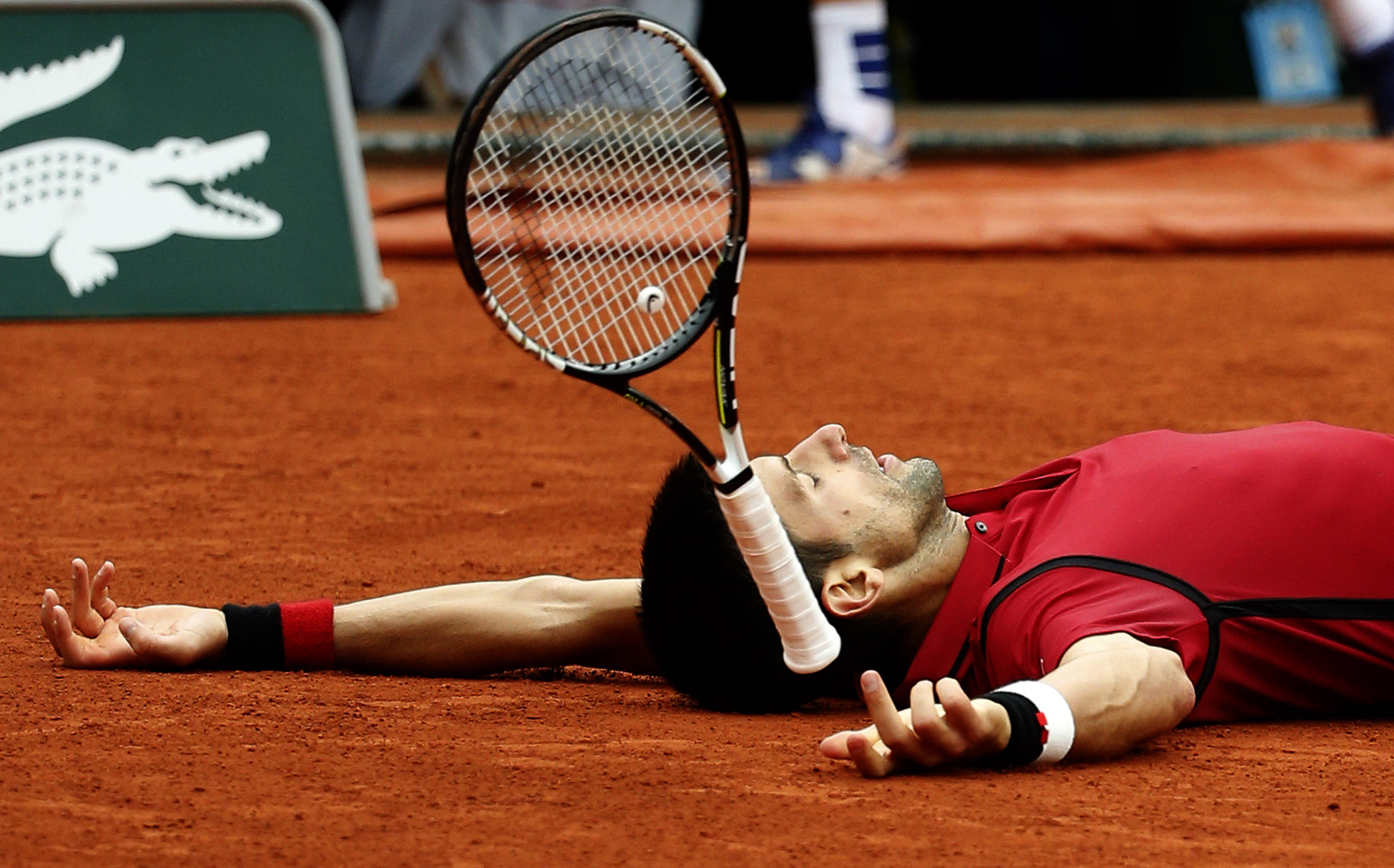 Serbia's Novak Djokovic falls as he defeats Britain's Andy Murray during their final match of the French Open tennis tournament at the Roland Garros stadium.