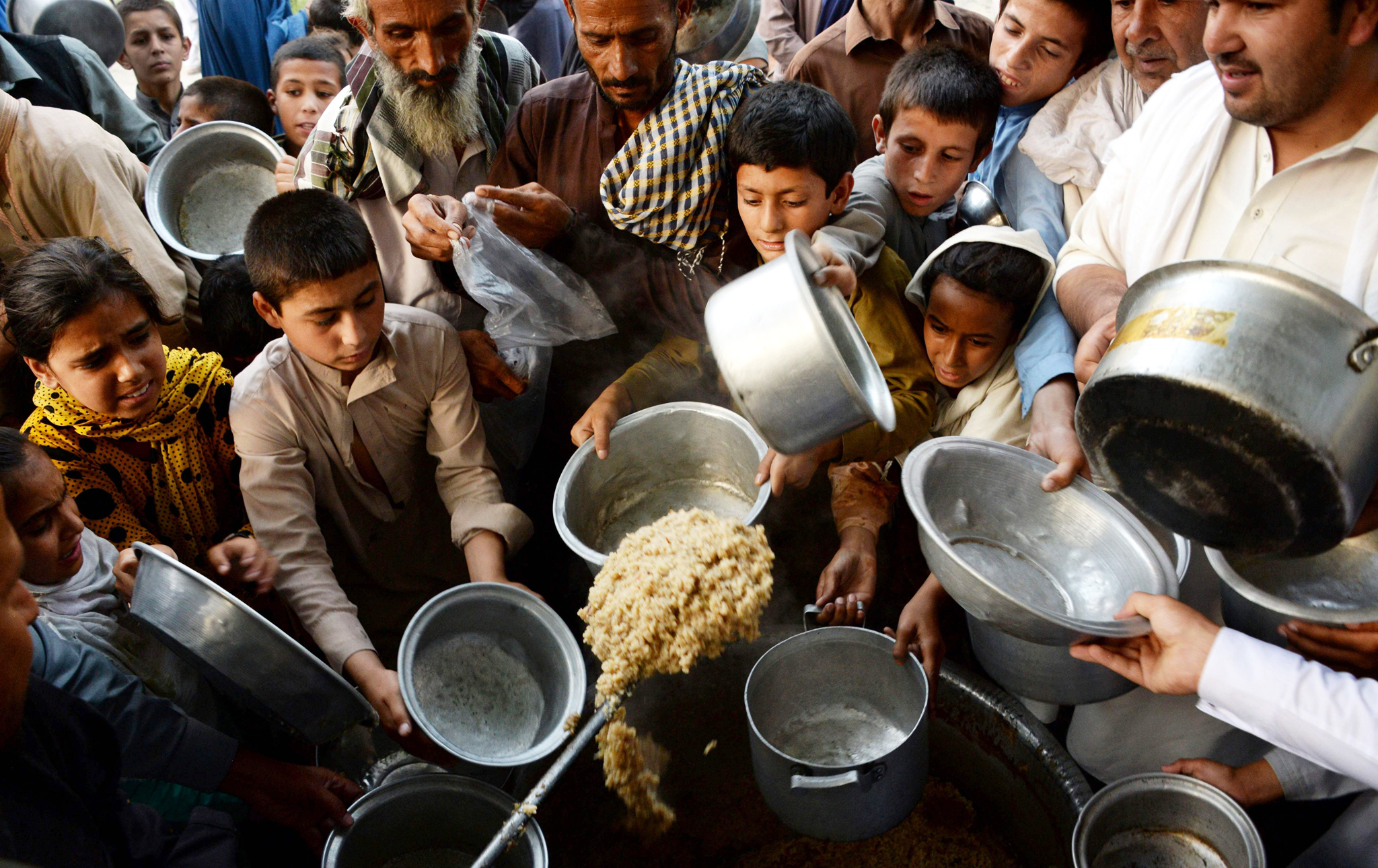 In this photograph taken on June 9, 2016, Afghan children hold dishes as they wait to receive food donated by a private charity for the needy during the Islamic holy month of Ramadan in the city of Jalalabad.    Across the Muslim world, the faithful fast from dawn to dusk and strive to be more pious during the holy month, which ends with the Eid holiday. / AFP PHOTO / NOORULLAH SHIRZADANOORULLAH SHIRZADA/AFP/Getty Images