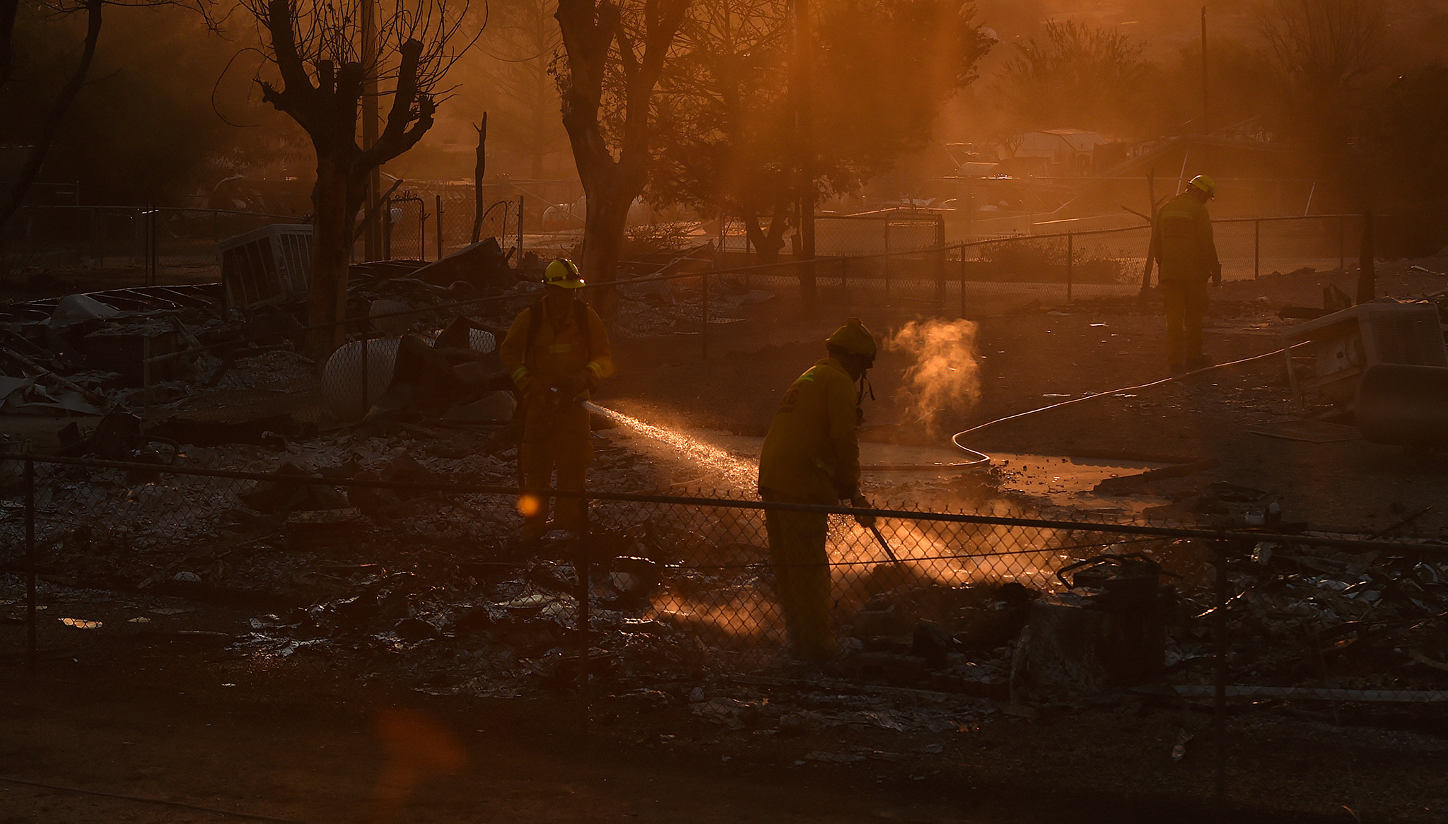 Firefighters mop-up a hot spot  at a residence levelled by the Erskine Fire in South Lake, California, USA