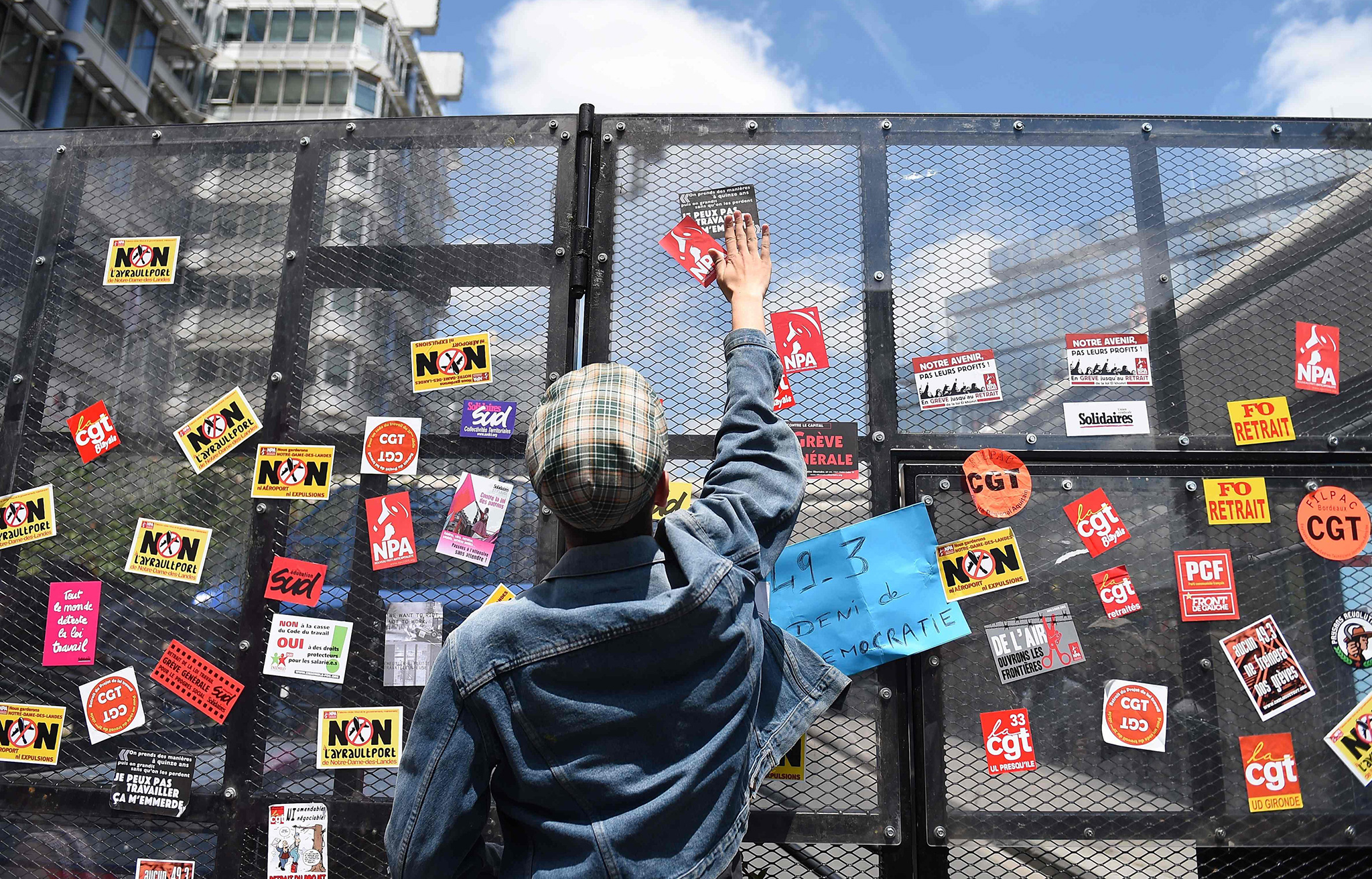 A demonstrator put stickers on an anti riot wall during a demonstration against proposed labour law reforms in Bordeaux, France