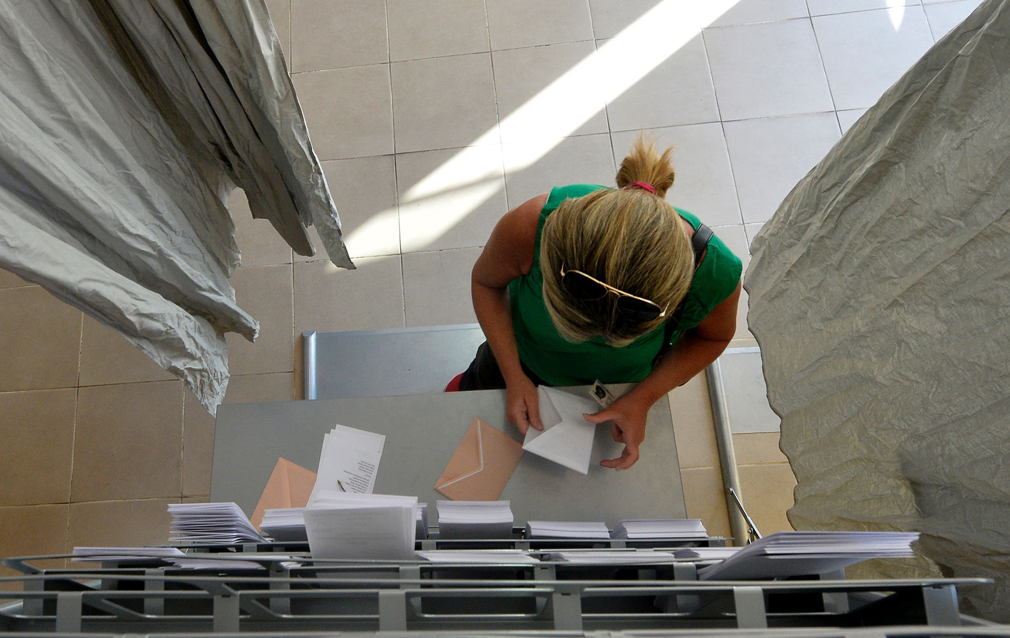 A woman prepares her ballot in a polling booth before voting in Spains general election at the Bernadette college polling station in Moncloa-Aravaca, Madrid