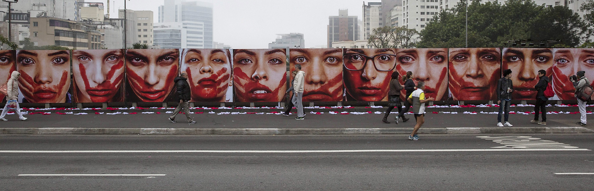 epa05354836 A group of people walk next to an installation by NGO Rio de Paz that shows pictures of models representing women victims of sexual attacks and 420 underpants that represent the 420 Brazilian women raped in the country every 72 hours, outside the Sao Paulo Arts Museum in Sao Paulo, Brazil, 10 June 2016.  EPA/SEBASTIAO MOREIRA