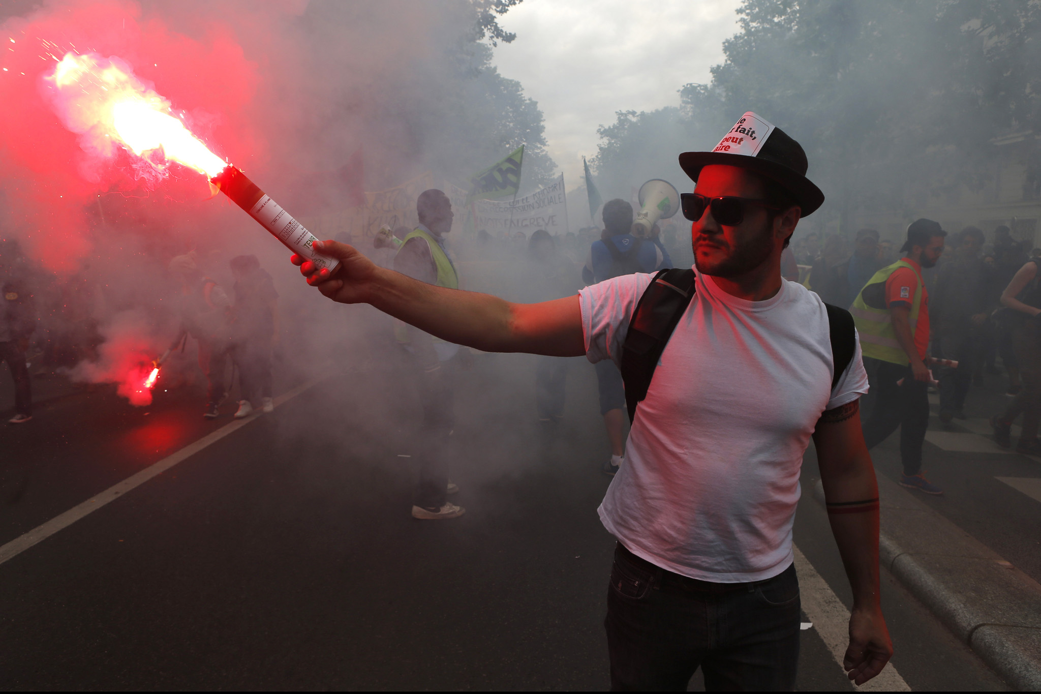 A member of the leftist CGT labor union holds a flare during a march in Paris Tuesday, June 14, 2016. Street protests are planned across France, rail workers and taxi drivers are going on strike and the Eiffel Tower is due to be closed as part of a protest against a reform aimed at loosening the country's labor rules. (AP Photo/Francois Mori)