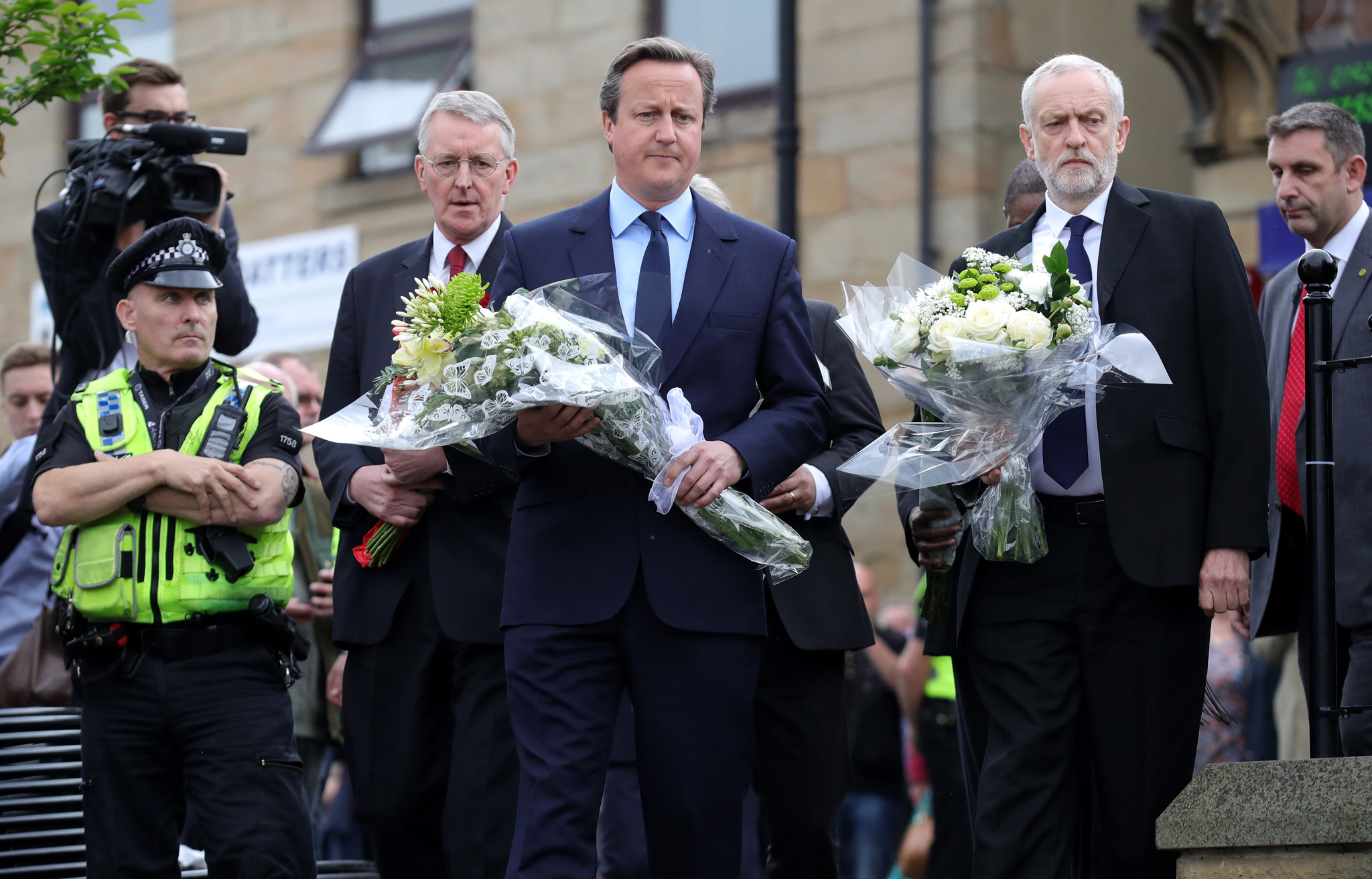 Tributes Paid To Murdered Labour MP Jo Cox...BIRSTALL, UNITED KINGDOM - JUNE 17:  Prime Minister David Cameron (C) and Labour Leader Jeremy Corbyn (R) arrive to pay their respects at the scene of the murder of Jo Cox, 41, Labour MP for Batley and Spen, who was shot and stabbed yesterday at her constituency surgery, on June 17, 2016 in Birstall, United Kingdom. The Labour MP for Batley and Spen was about to hold her weekly constituency surgery in Birstall Library yesterday on June 16, 2016, when she was shot and stabbed in the street. A 52-year old man is being held in Police custody in connection with the death.  (Photo by Christopher Furlong/Getty Images)