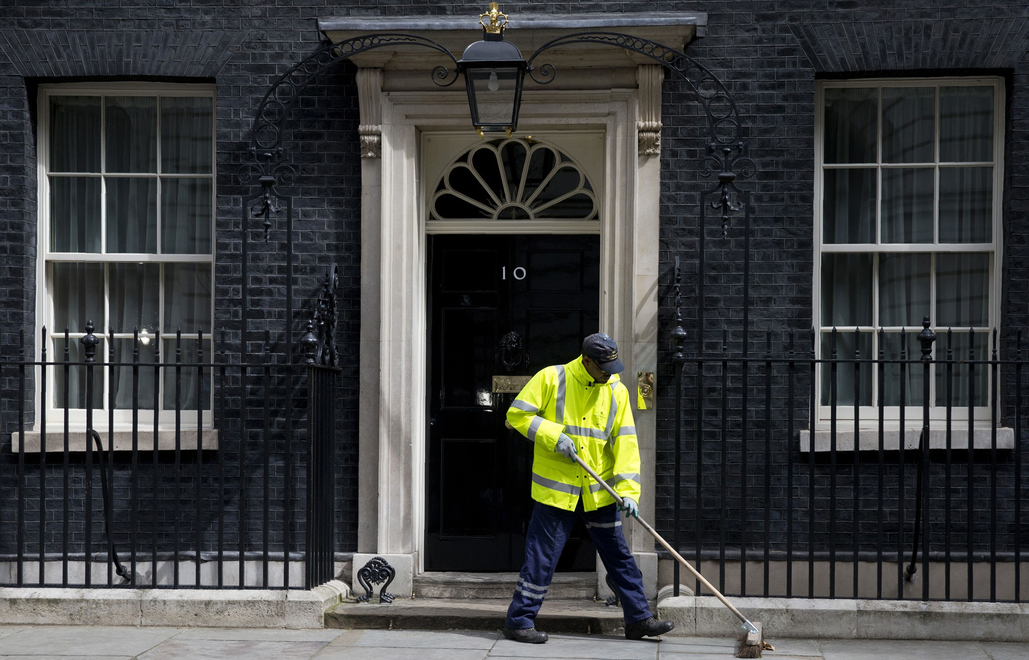 A City of Westminster worker sweeps the pavement outside 10 Downing Street in central London on June 25, 2016. The result of Britain's June 23 referendum vote to leave the European Union (EU) has pitted parents against children, cities against rural areas, north against south and university graduates against those with fewer qualifications. London, Scotland and Northern Ireland voted to remain in the EU but Wales and large swathes of England, particularly former industrial hubs in the north with many disaffected workers, backed a Brexit. / AFP PHOTO / JUSTIN TALLISJUSTIN TALLIS/AFP/Getty Images