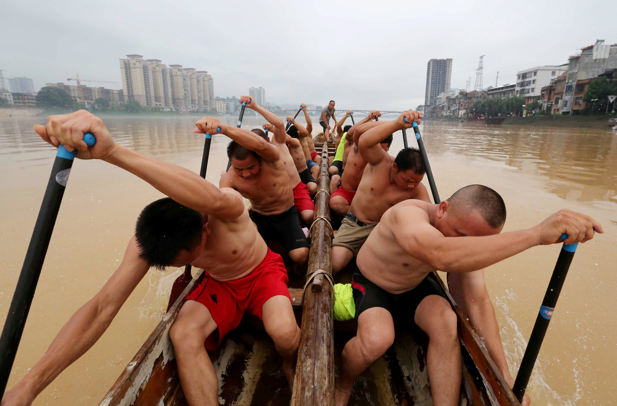 People participate during a training session on a river ahead of a local dragon boat competition in Liuzhou, Guangxi Zhuang Autonomous Region, China, June 14, 2016. REUTERS/Stringer ATTENTION EDITORS - THIS IMAGE WAS PROVIDED BY A THIRD PARTY. EDITORIAL USE ONLY. CHINA OUT. NO COMMERCIAL OR EDITORIAL SALES IN CHINA.