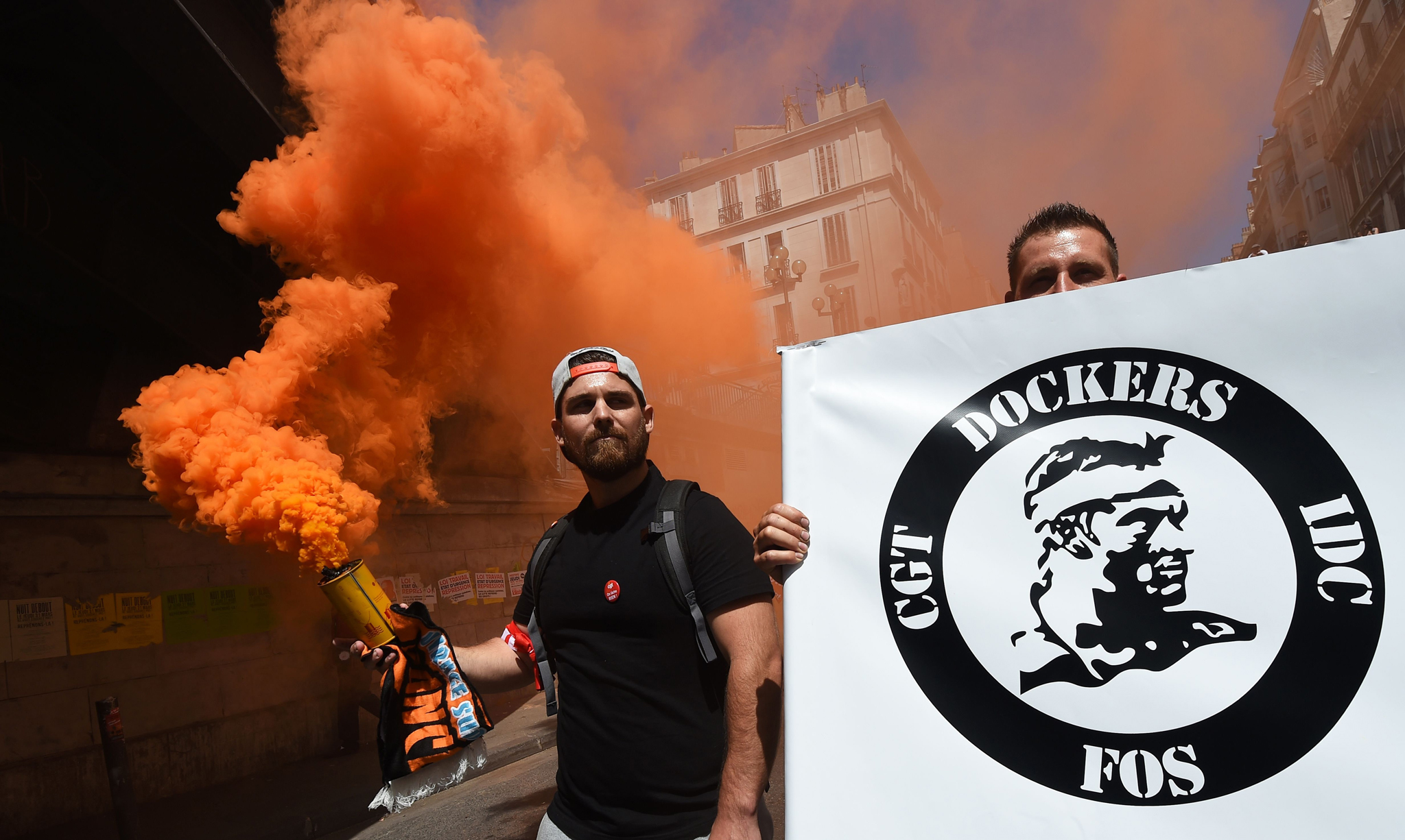 Protestors hold a smoke bomb and a placard of the French General Confederation of Labour (CGT) worker's union of the dockers branch during a demonstration against the French government's planned labour law reforms on June 23, 2016 in Marseille, southern France. Unions are protesting a series of labour market reforms that Valls had to force through parliament in May to avoid a vote, even after the bill was significantly watered down. However after more than three months of protests and strikes over the legislation, neither side is willing to budge. / AFP PHOTO / ANNE-CHRISTINE POUJOULATANNE-CHRISTINE POUJOULAT/AFP/Getty Images
