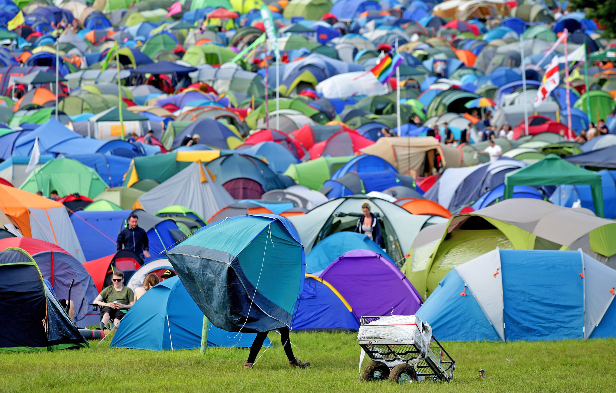 A festivalgoer carrying a tent at the Glastonbury Festival, at Worthy Farm in Somerset. PRESS ASSOCIATION Photo. See PA story SHOWBIZ Glastonbury. Picture date: Wednesday June 22, 2016