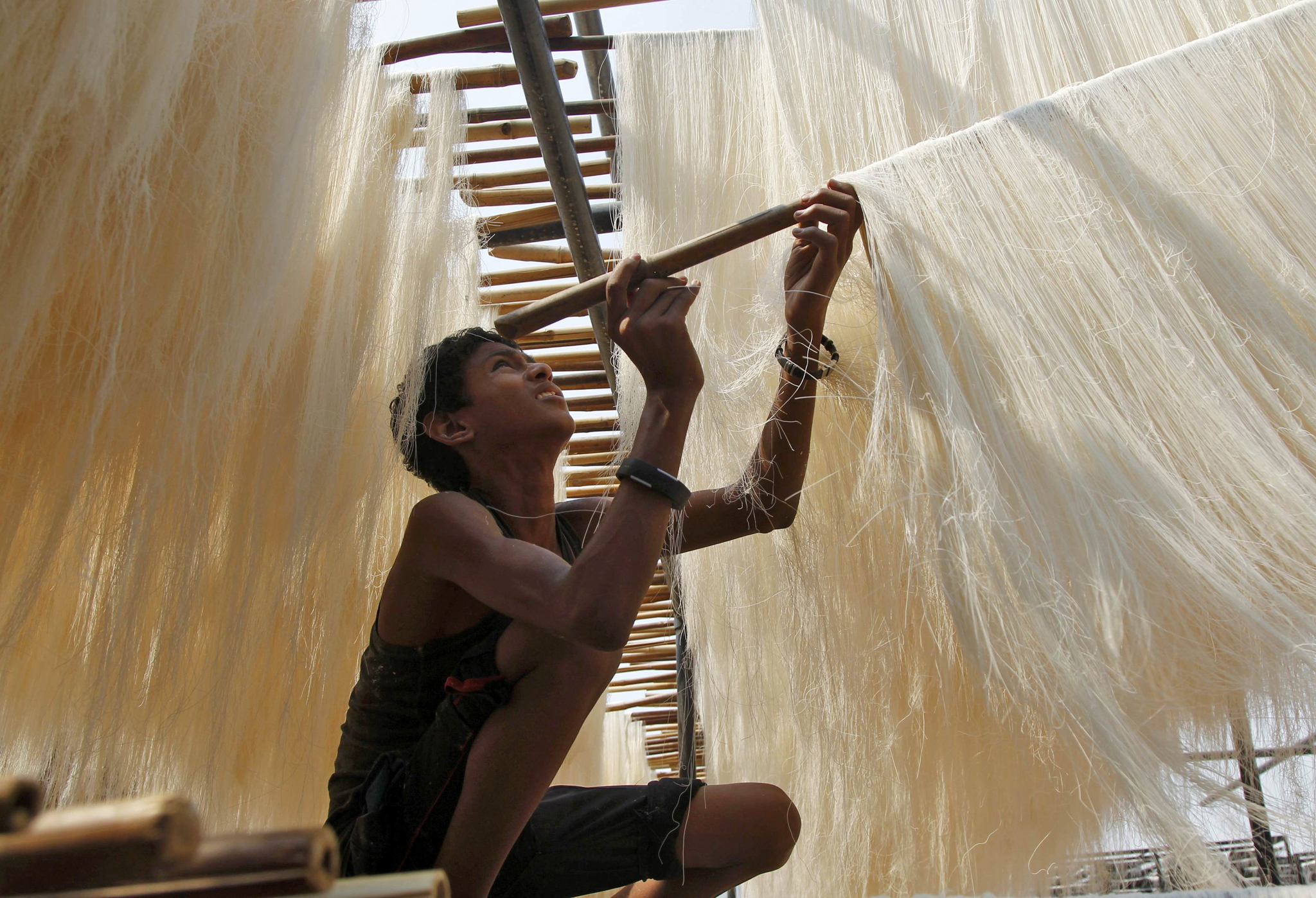 A boy hangs strands of vermicelli, a specialty eaten during the Muslim holy fasting month of Ramadan, to dry at a factory in Allahabad, India, June 7, 2016. REUTERS/Jitendra Prakash