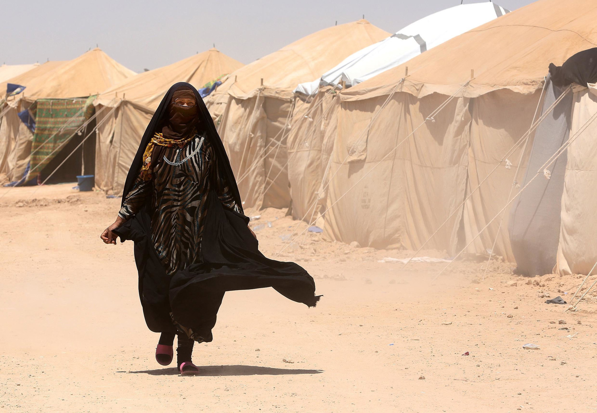 An Internally displaced woman arrives to a camp outside Fallujah, Iraq, Monday, June 14, 2016. The U.N. estimates about 50,000 civilians are trapped inside the city and that 42,000 people have fled Fallujah since a military operation to retake the city began in late May. Organizations such as MSF and The Norwegian Refugee Council say the number of those who've fled is closer to 30,000, lower than the U.N. estimate. (AP Photo/Hadi Mizban)