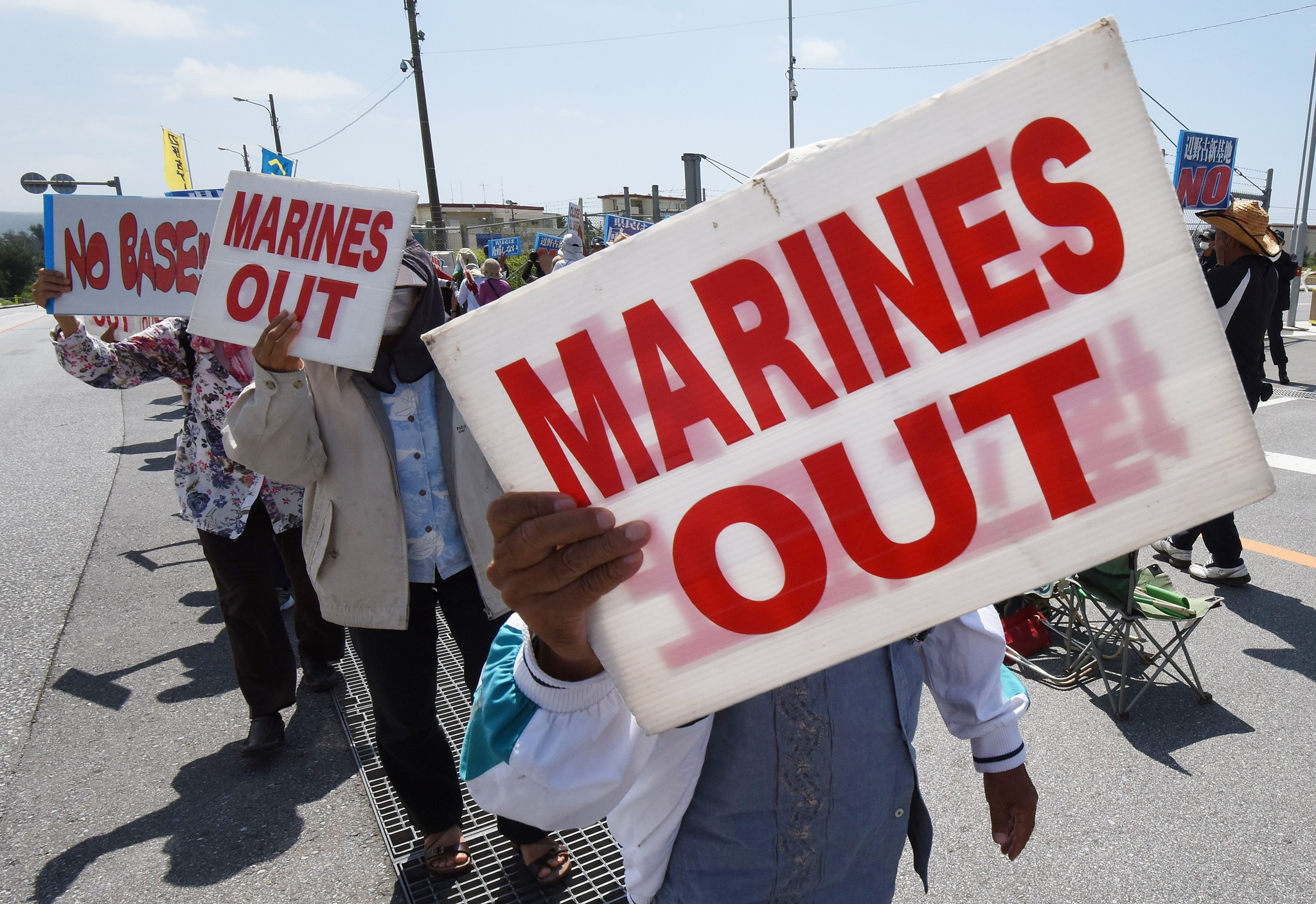 People hold placards as they protest against the presence of US bases, in front of the gate of the US Marine Corps' Camp Schwab in Nago on the southern island of Okinawa prefecture on June 17, 2016. Okinawan