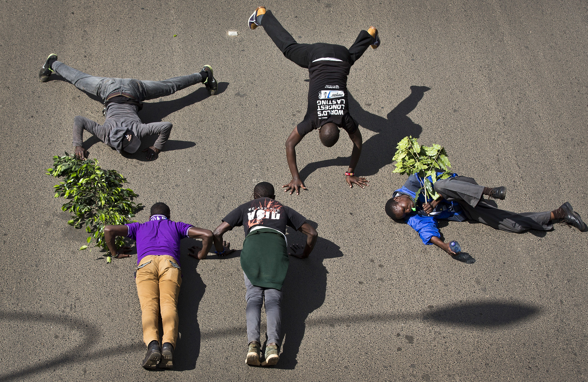 Demonstrators calling for the disbandment of the national electoral commission over allegations of bias and corruption, perform press-ups in the street as a sign of strength, in downtown Nairobi, Kenya Monday, June 6, 2016. While demonstrations led by opposition leaders in the capital were largely peaceful, police in Kisumu tear-gassed demonstrators who responded by throwing stones and witnesses say some people were killed by police.