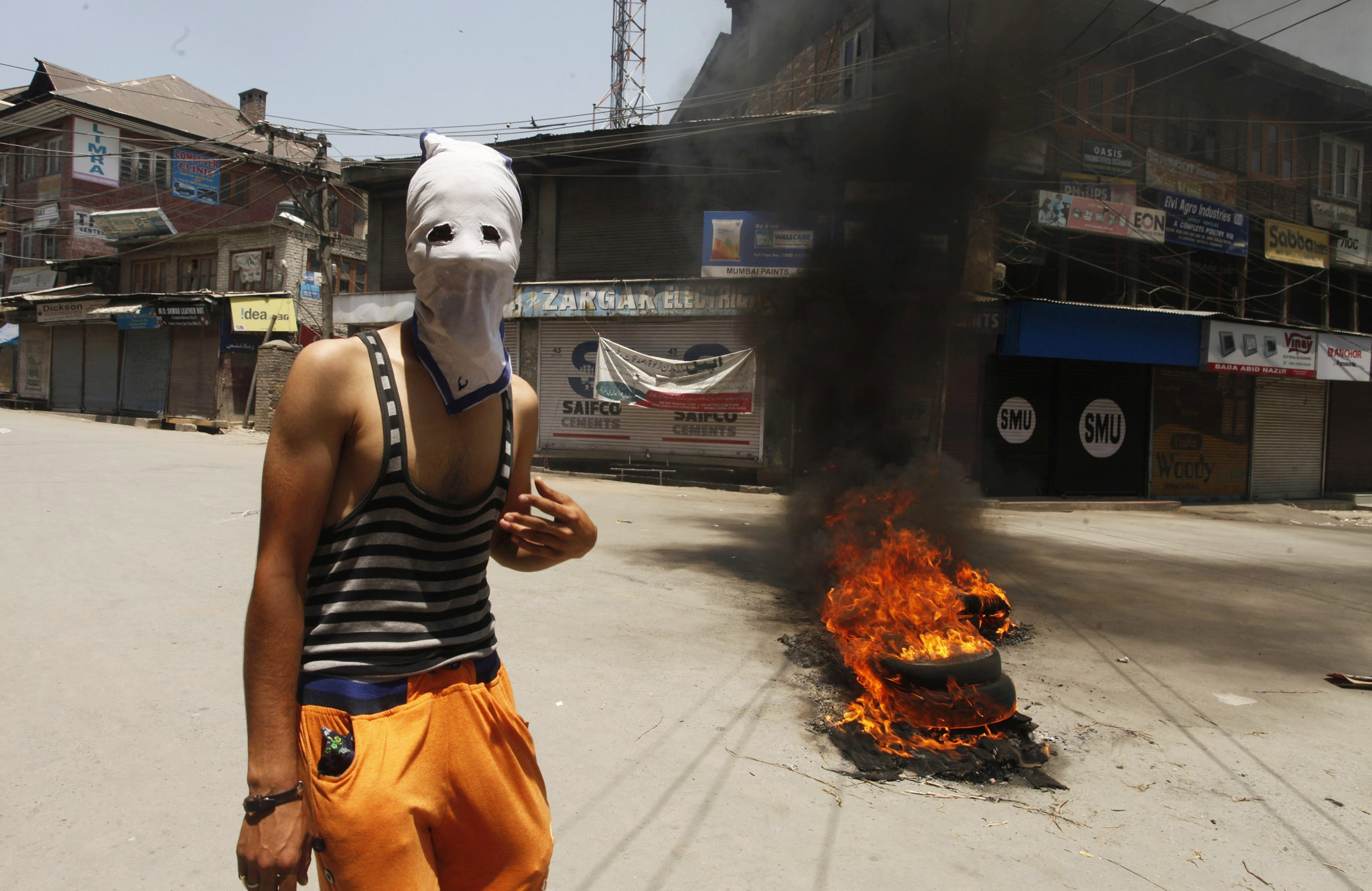 epa05389229 A masked Kashmiri Muslim stands near burning tires during a protest in Srinagar, the summer capital of Indian Kashmir, 25 June 2016. According to local news reports, clashes broke out between the Indian Police and protesters in Maisuma area of Srinagar when a protest march of separatists was not allowed to reach Lal Chowk, the city centre. The separatists had called for a protest in Lal Chowk against what they call conspiracies to change the demography of the Muslim-majority Jammu Kashmir by setting up Sainik colonies (Colonies for retired Indian Army men) and separate township for displaced Kashmiri Pandits (Hindus).  EPA/EPA
