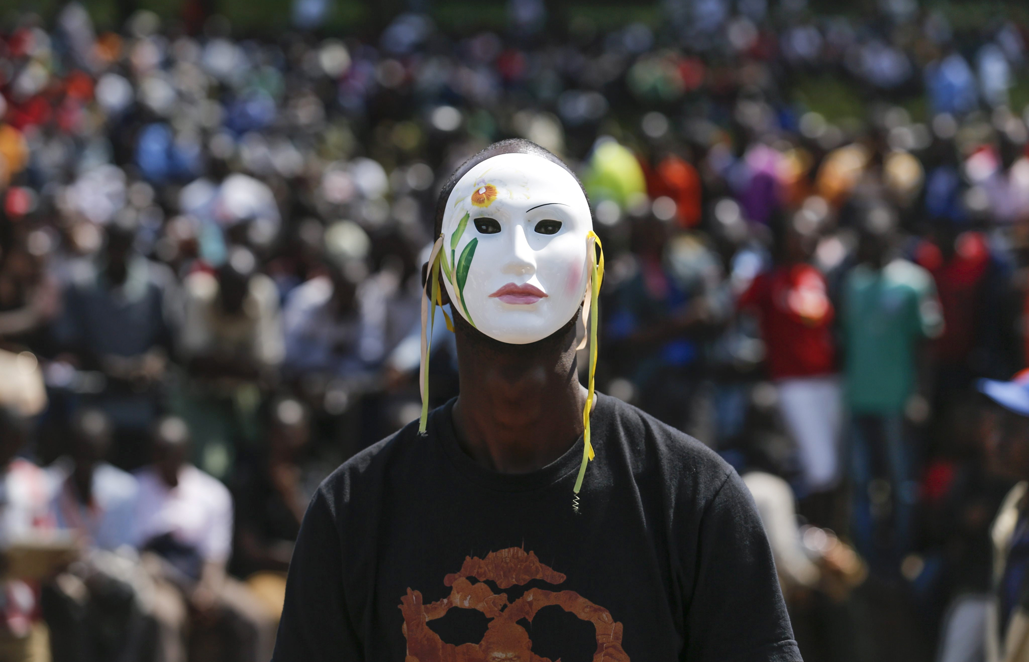 epa05340705 A supporter of the opposition Coalition for Reforms and Democracy (CORD), led by former Prime Minister Raila Odinga, wears a mask and looks on during a rally held in Nairobi, Kenya, 01 June 2016. Kenyan opposition staged a rally on Madaraka Day, the national holiday to commemorate the day that Kenya attained internal self-rule from Britain in 1963, to protest against the country's electoral body Independent Electoral and Boundaries Commission (IEBC) and push for reforms ahead of the next year's general elections.  EPA/DAI KUROKAWA