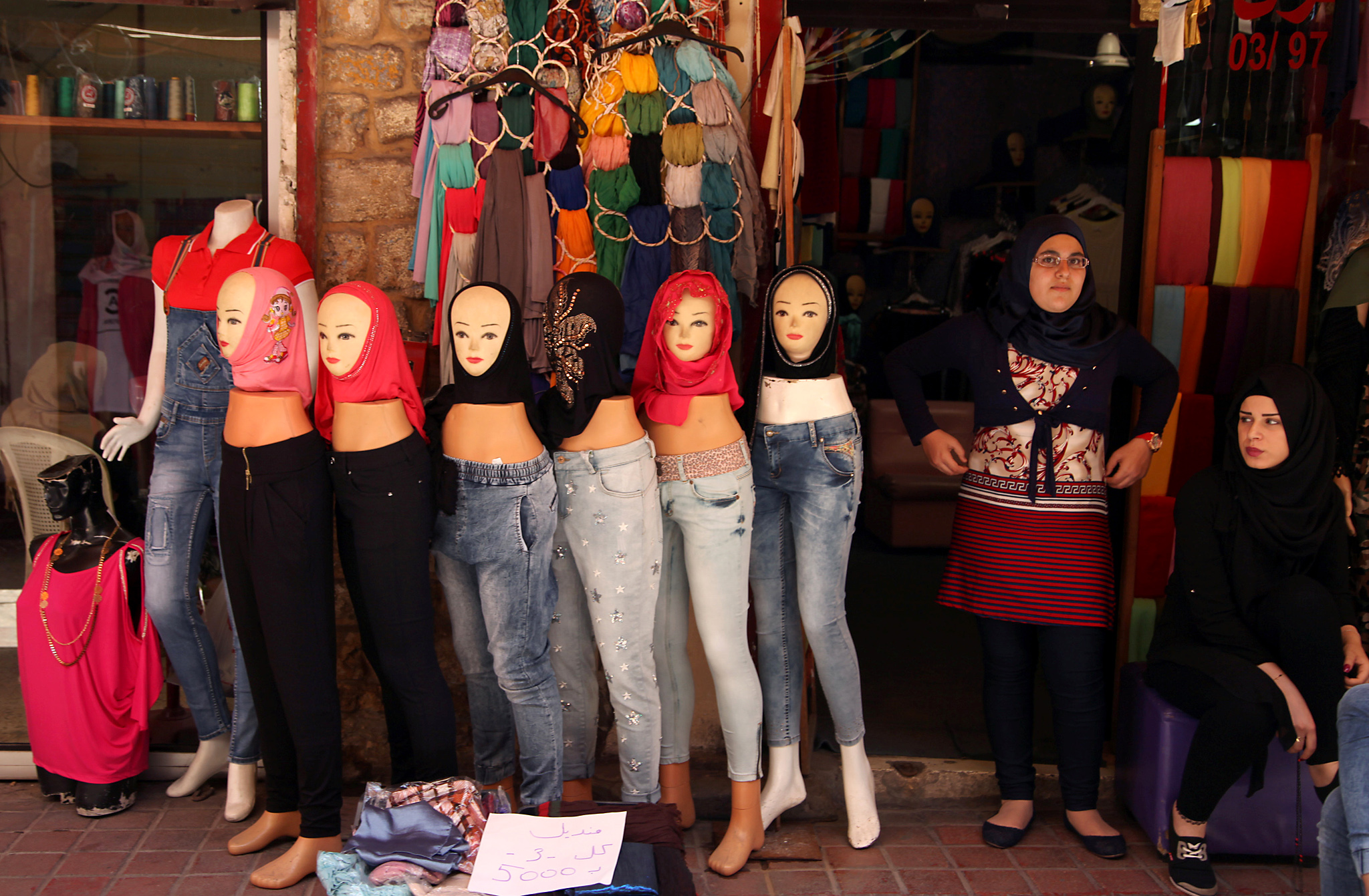 Women stand outside their shop near veils displayed on mannequins for sale during the holy month of Ramadan in Tyre old city, southern Lebanon June 12, 2016. Picture taken June 12, 2016. REUTERS/Ali Hashisho