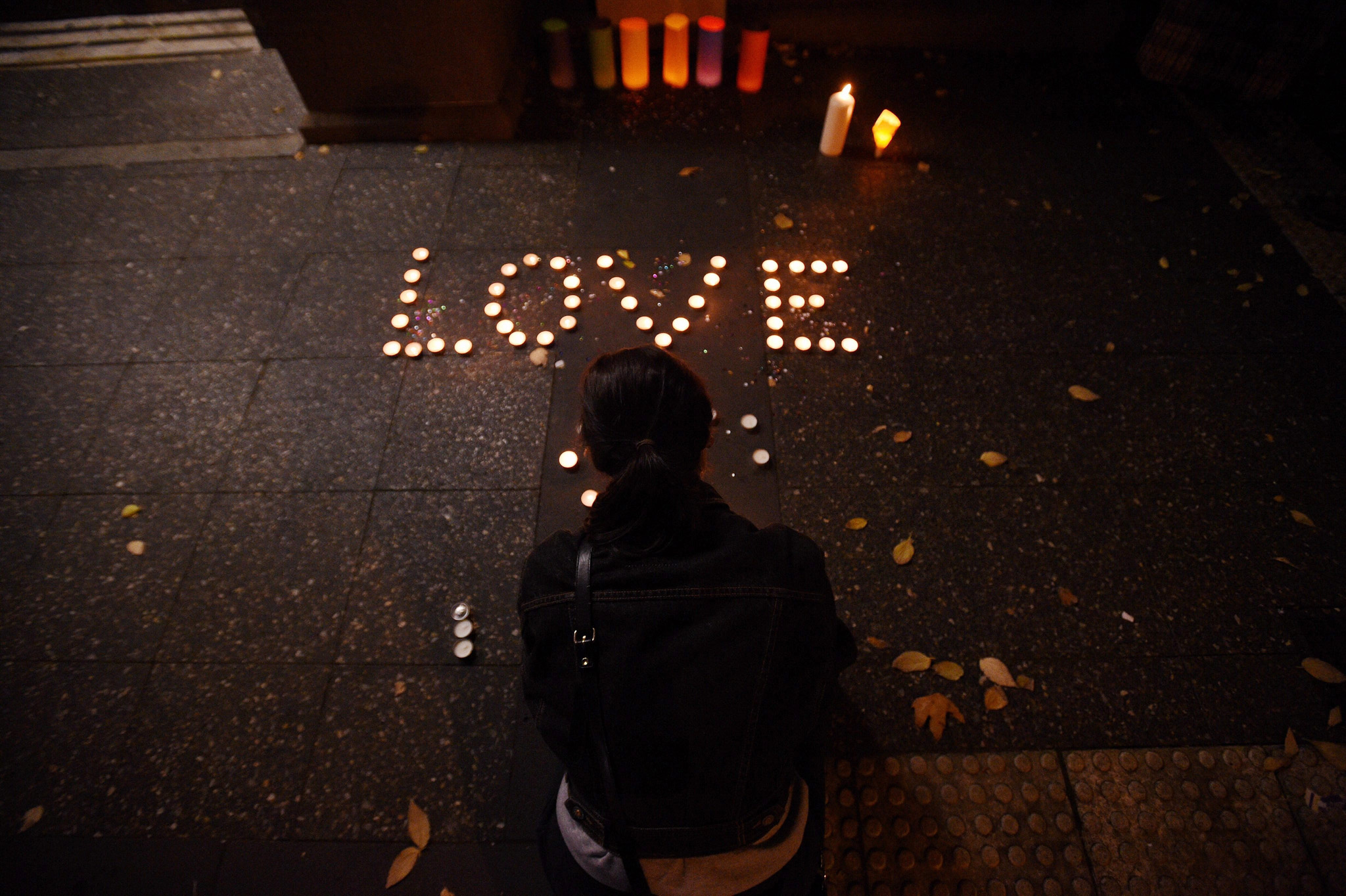 epa05360992 A woman places a candle to mourn, honor and remember the victims of the Orlando nightclub shooting at Newtown, in Sydney, Australia, 13 June 2016. At least 50 people were killed and 53 were injured in a shooting attack at an LGBT club in Orlando, Florida, in the early hours of 12 June. The shooter, Omar Mateen, 29, a US citizen of Afghan descent, was killed in an exchange of fire with the police after taking hostages at the club.  EPA/SAM MOOY AUSTRALIA AND NEW ZEALAND OUT