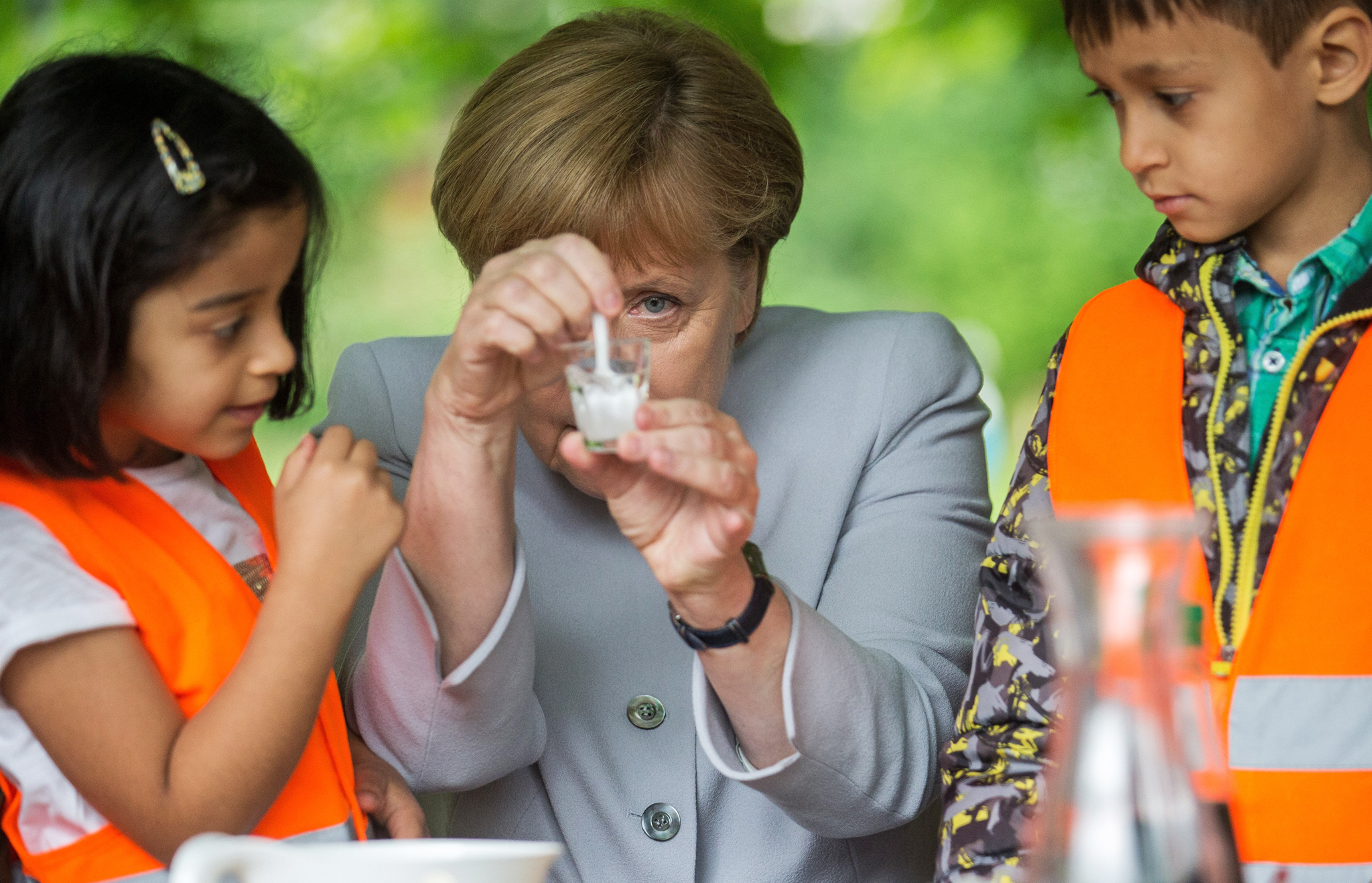 German Chancellor Angela Merkel watches how lemonade is mixed as part of a children's experiment during her visit at a kindergarten in Berlin, Germany, Tuesday, June 21, 2016