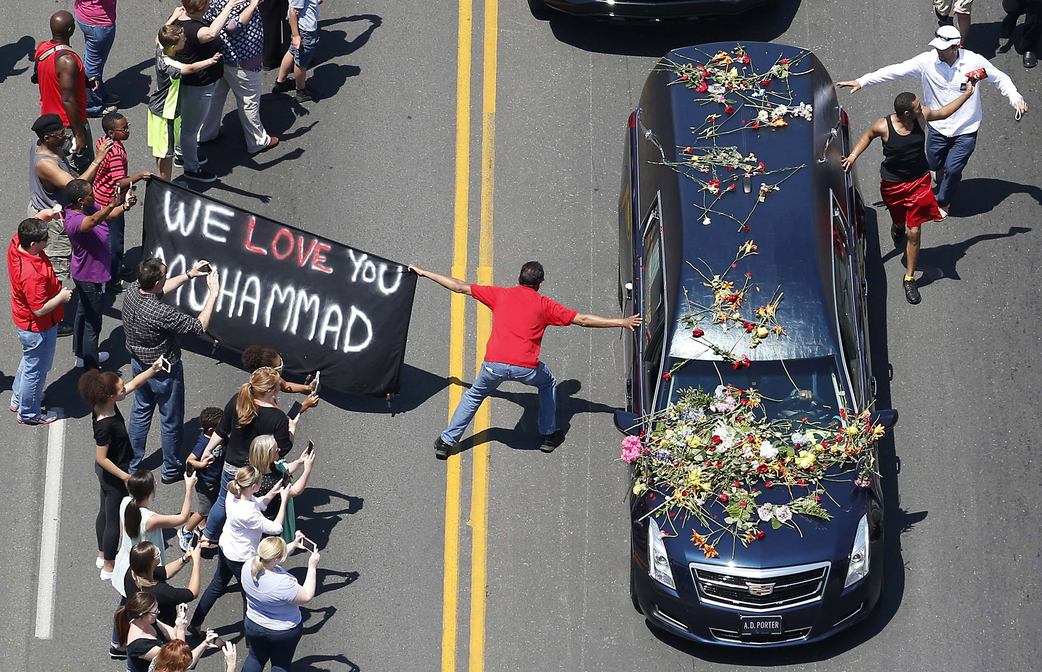 A well-wisher holding a banner touches the hearse carrying the remains of Muhammad Ali during the funeral procession for the three-time heavyweight boxing champion in Louisville, Kentucky, U.S., June 10, 2016.   REUTERS/Adrees Latif