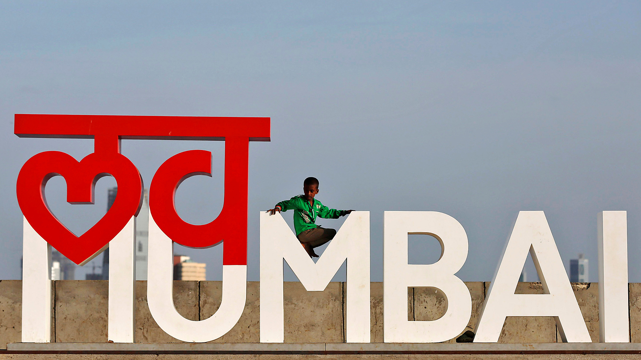 """A boy plays on an installation at a wall along the sea front promenade in Mumbai, India June 2, 2016.  The installation reads """"Love Mumbai"""". REUTERS/Shailesh Andrade"""