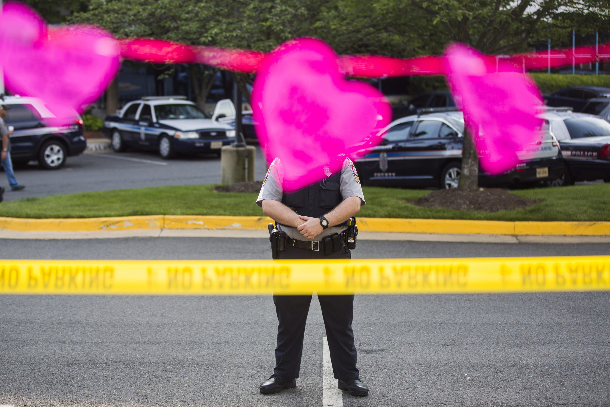 epa05381363 A Fairfax County police officer outside the headquarters of the National Rifle Association (NRA) beneath a paper heart inscribed with the name of a victim of the Orlando shooting massacre in Fairfax, VA, USA, 21 June 2016. On 20 June, the US Senate failed to pass four gun control amendments in the wake of the largest mass shooting in US history.  EPA/JIM LO SCALZO