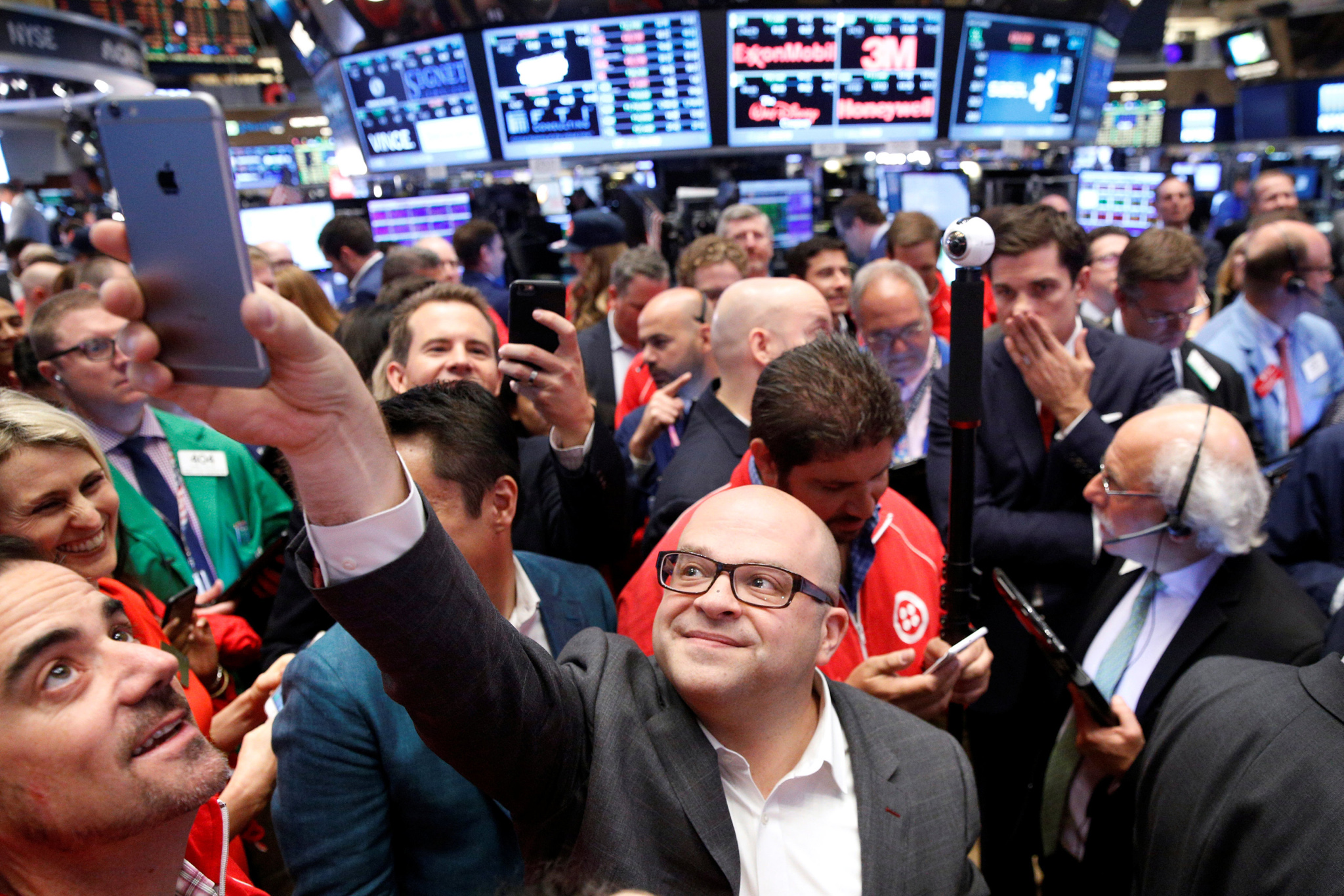 Jeff Lawson, (C) Founder, CEO, & Chairman of Communications software provider Twilio Inc., takes a selfie photo during his company's IPO on the floor of the New York Stock Exchange (NYSE) in New York City, U.S., June 23, 2016. REUTERS/Brendan McDermid