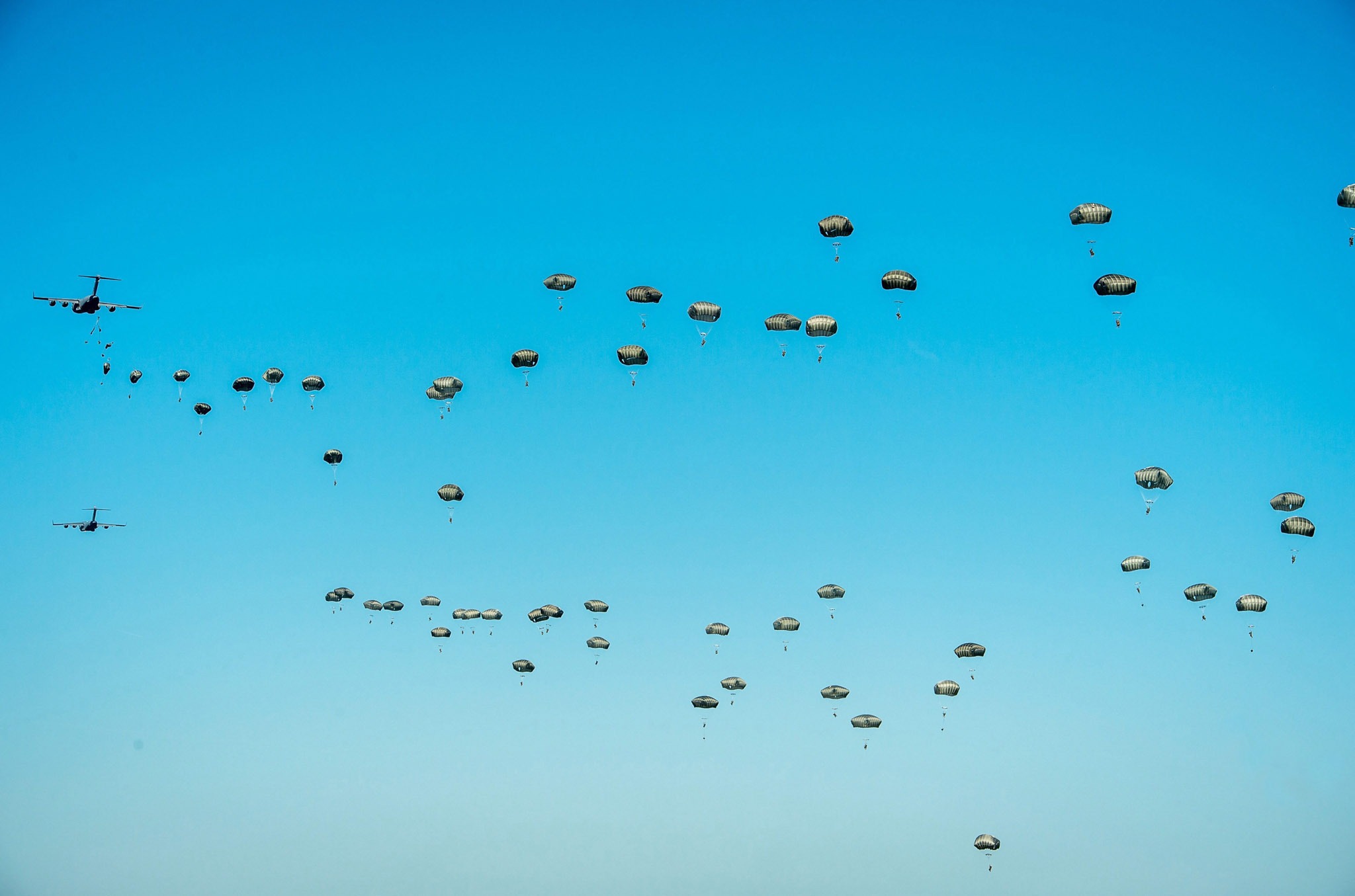 epa05350322 US Army C-17 Globemaster military transport planes drop US paratroopers from the 82 Airborne Division during the Swift Response-16 part of the NATO Anaconda-16 exercise at the military area near Torun, Poland, 07 June 2016.  About 2 thousand paratroopers from Poland, USA and Great Britain took part in a landing exercise as part of the The Polish-led multinational exercise Anaconda-16, conducted with allies and partners from 24 countries between 07 and 17 June 2016, which is to test and enhance the capabilities of NATO countries to quickly respond to threats regardless of distance and origin.  EPA/TYTUS ZMIJEWSKI POLAND OUT