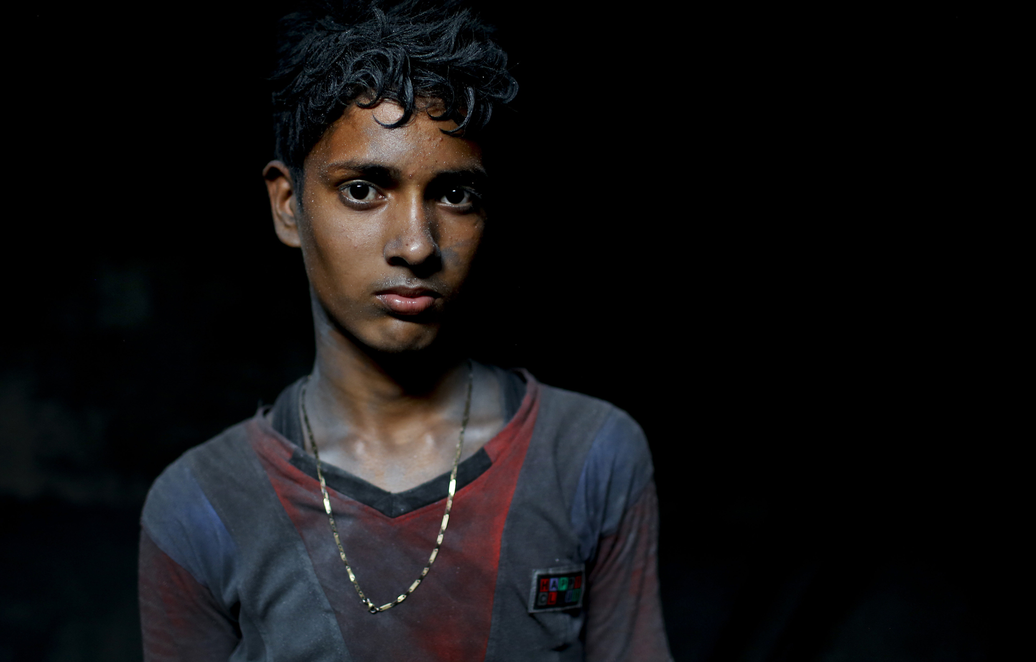 In this Sunday, June 12, 2016, photo, Nizam, 11, looks towards camera as he works at a factory that makes metal utensils in Dhaka, Bangladesh, Sunday, June 12, 2016. He earns less than $5 per week. The World Day Against Child Labor, which was initiated in 2002 by the International Labor Organization to highlight the plight of child laborers, is observed across the world on June 12. (AP Photo/ A.M. Ahad)