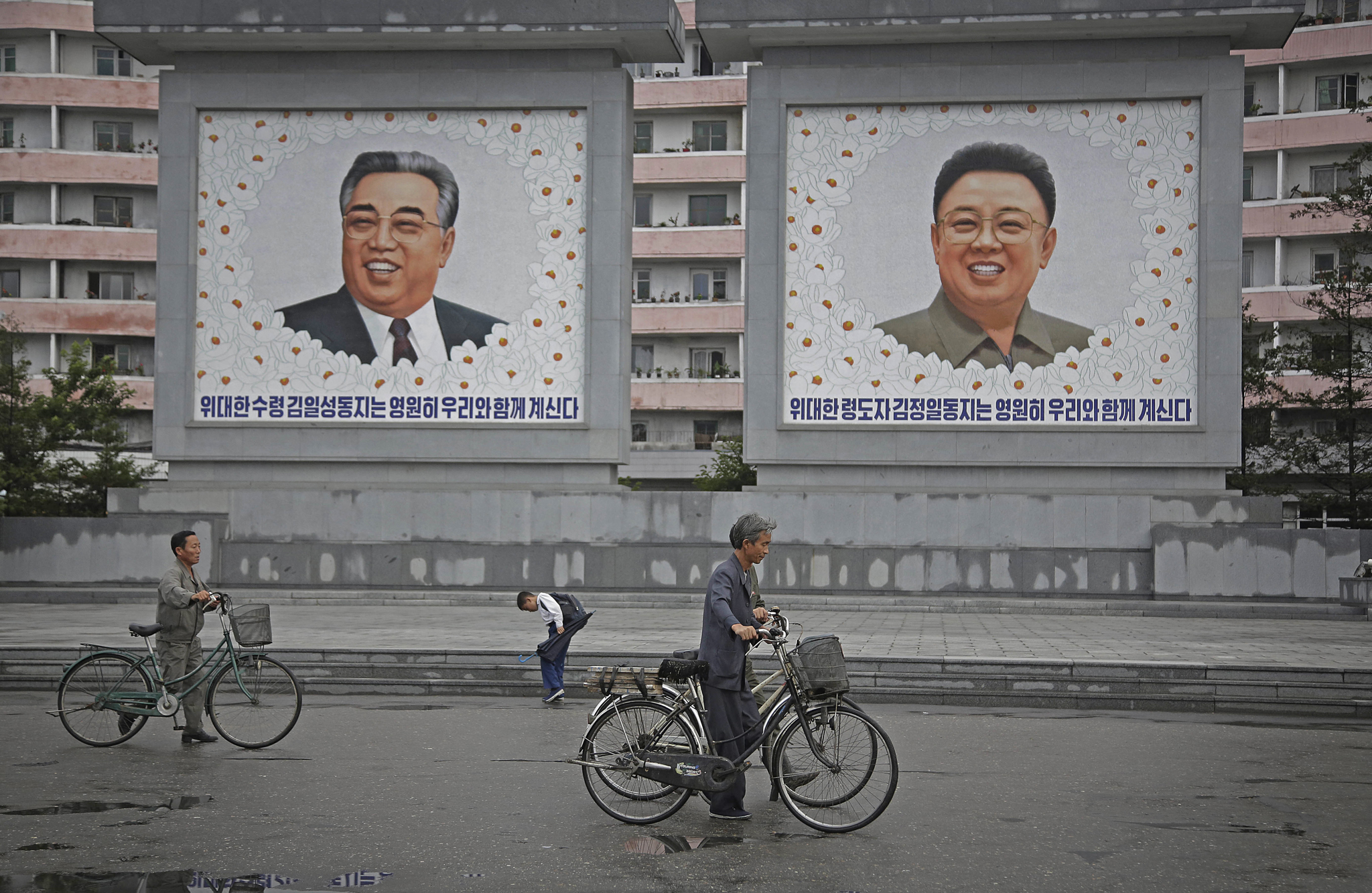 North Koreans push their bicycles past giant portraits of the late North Korean leaders Kim Il Sung and Kim Jong Il at the end of a work day on Wednesday, June 22, 2016, in Wonsan, North Korea.