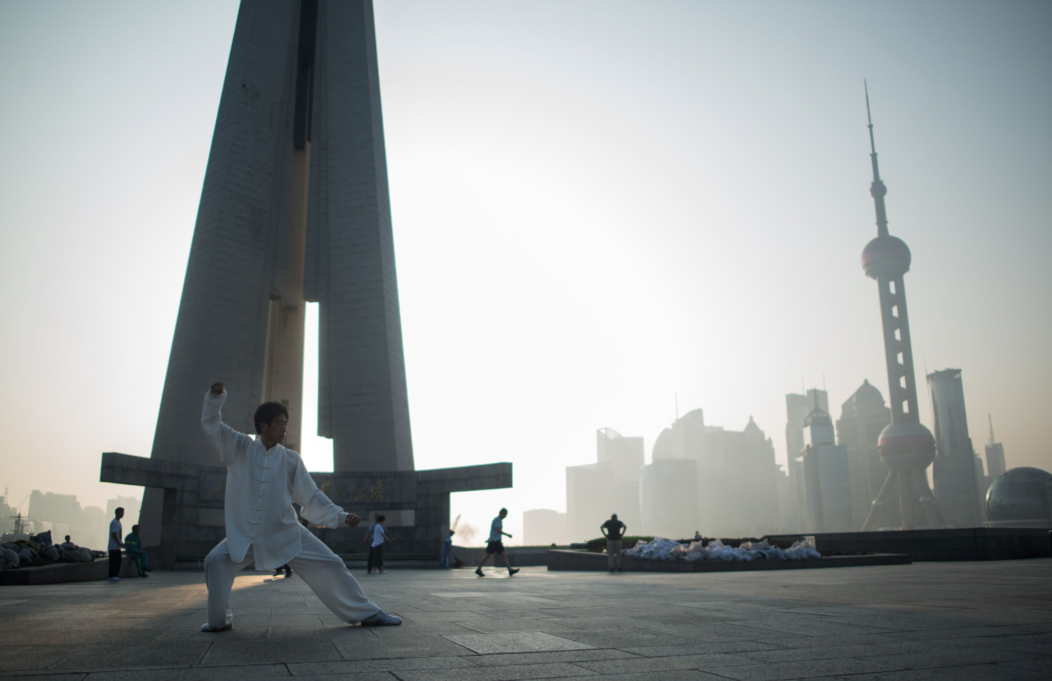 A man does excerices in front of the financial district of Lujiazui in Shanghai