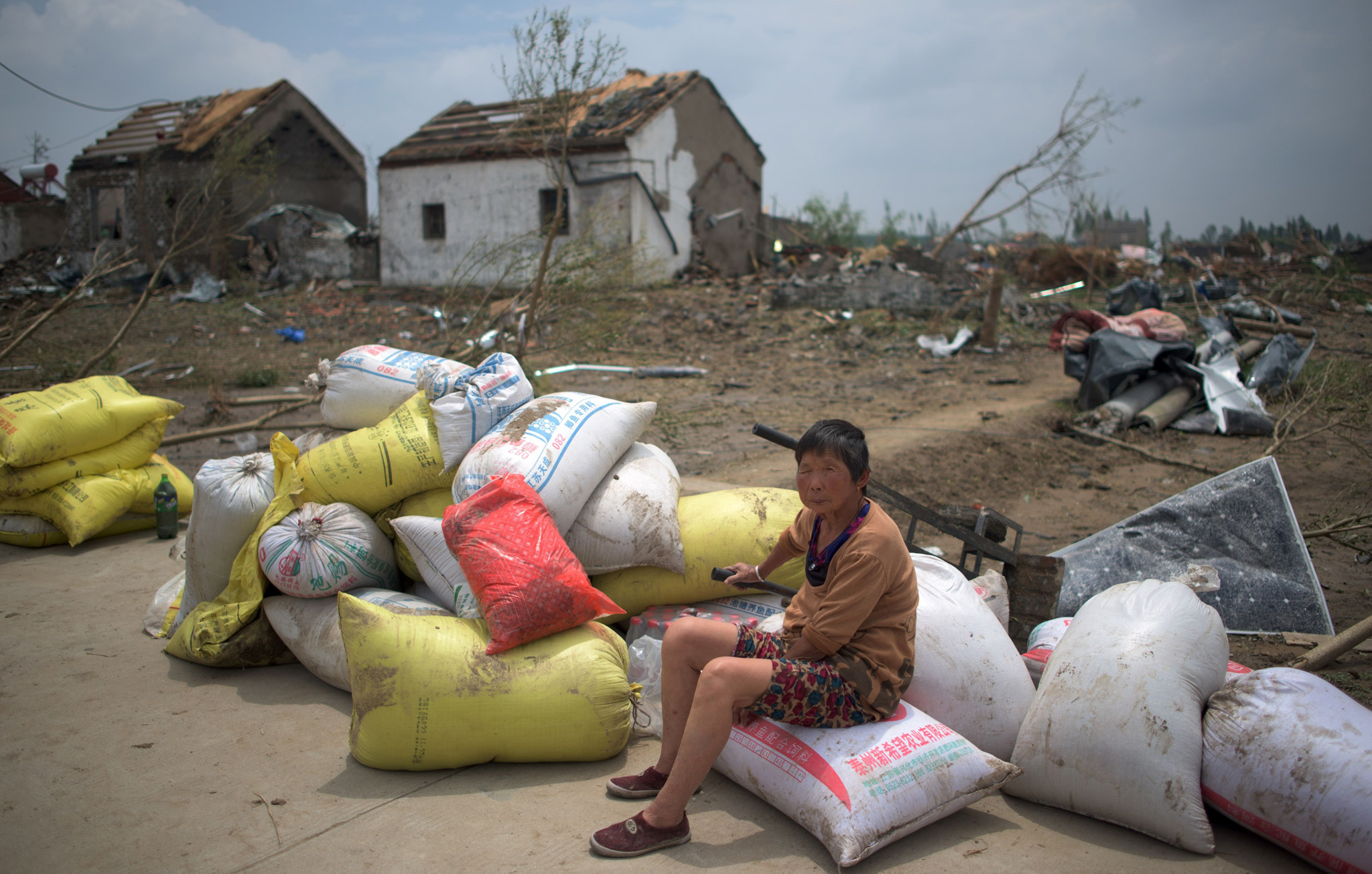 A woman sits with her belongings in front of the rubble of her destroyed houses after a tornado in Funing, in Yancheng, in China's Jiangsu province on June 24, 2016.   Extreme weather, including hailstorms, heavy rain and a tornado, killed 78 and injured dozens in China's eastern Jiangsu province, the official Xinhua news agency reported on June 23.