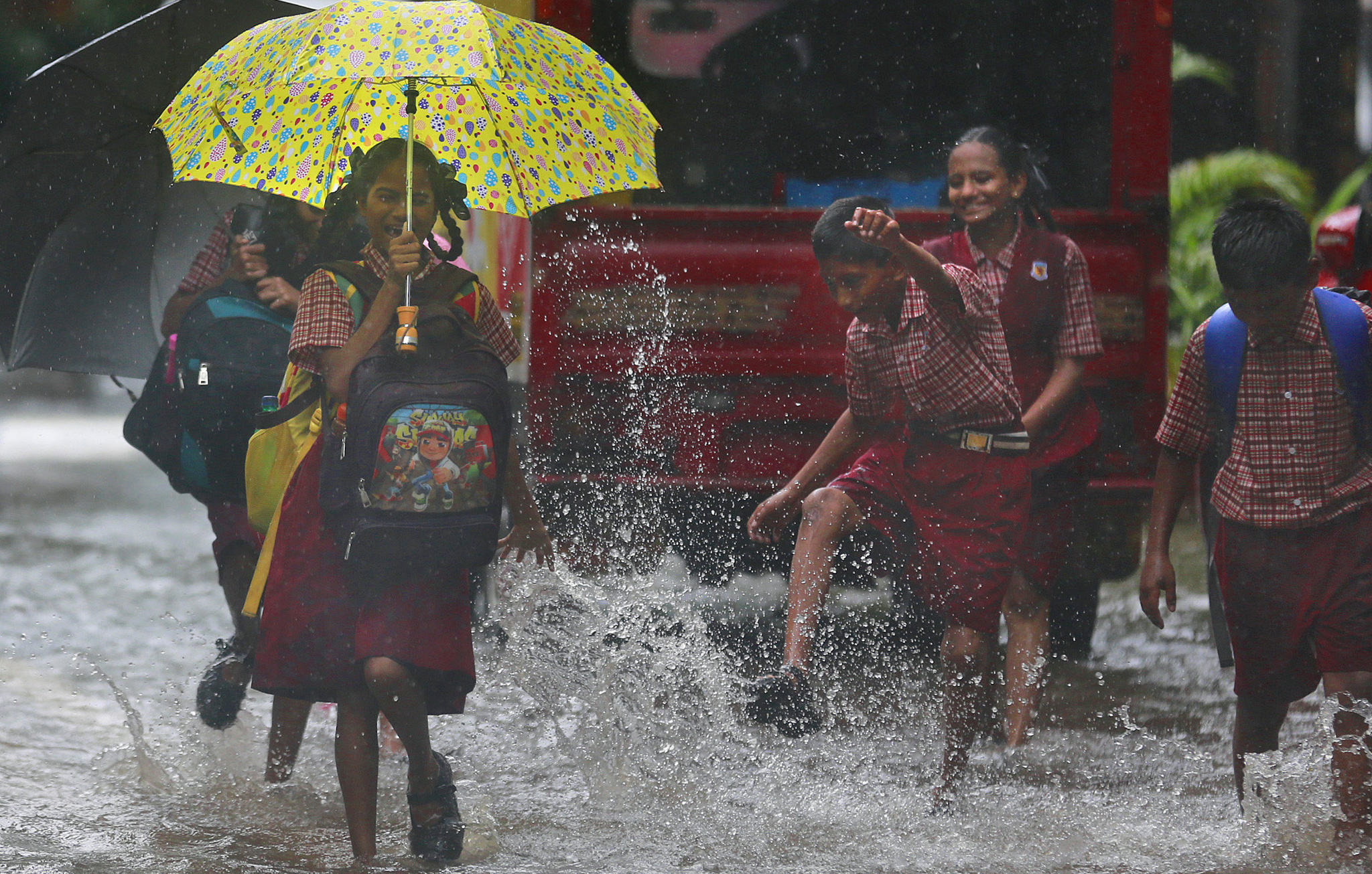 A schoolgirl reacts to rainwater being splashed on her, in a flooded street in Mumbai, India