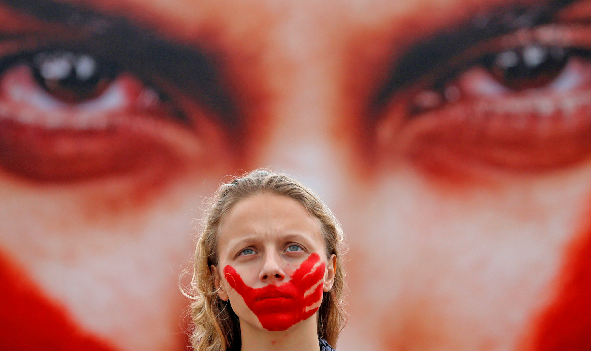 An activist poses for picture in front a photo from Brazilian photographer Marcio Freitas, during a protest by non-governmental organization (NGO) Rio de Paz (Rio of Peace) against rape and violence against women on Copacabana beach in Rio de Janeiro, Brazil, June 6, 2016.
