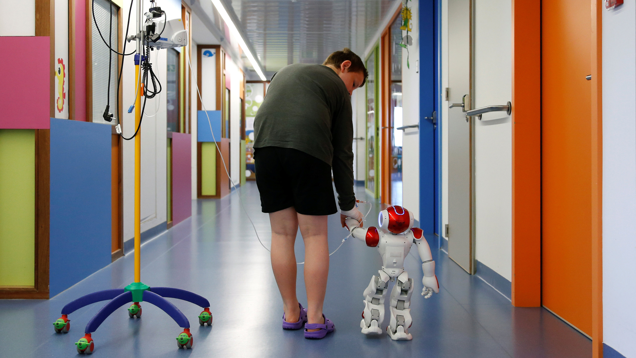 "Belgian Ian Frejean, 11, walks with ""Zora"" the robot, a humanoid robot designed to entertain patients and to support care providers, at AZ Damiaan hospital in Ostend, Belgium June 16, 2016. REUTERS/Francois Lenoir"